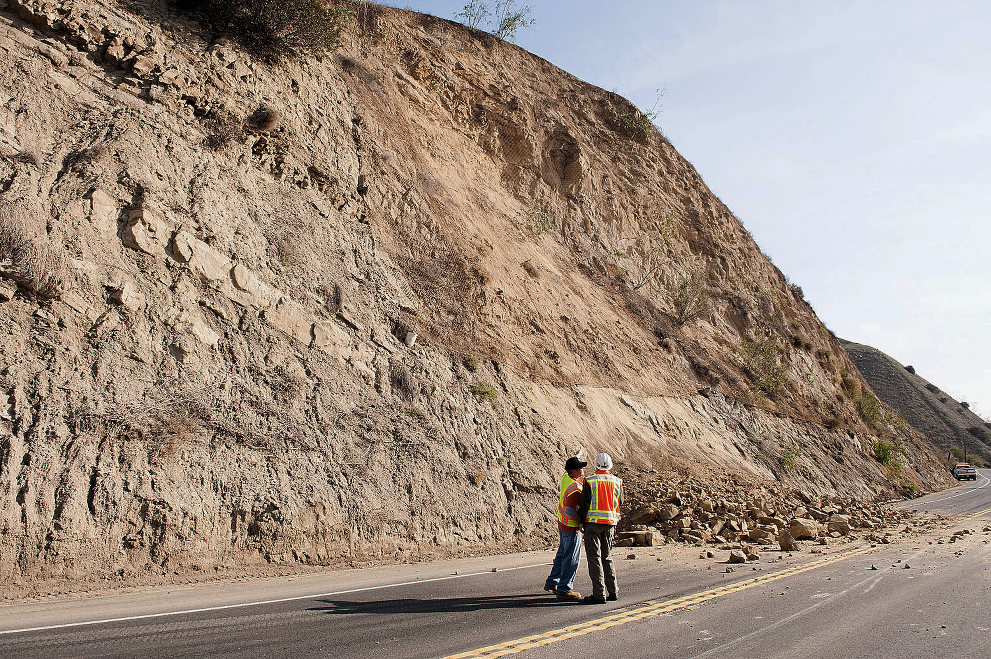 A CalTrans worker and a geologist look at a rock wall where a rockslide closed a road in Brea, Calif., on Saturday after an earthquake hit Orange County Friday night.
