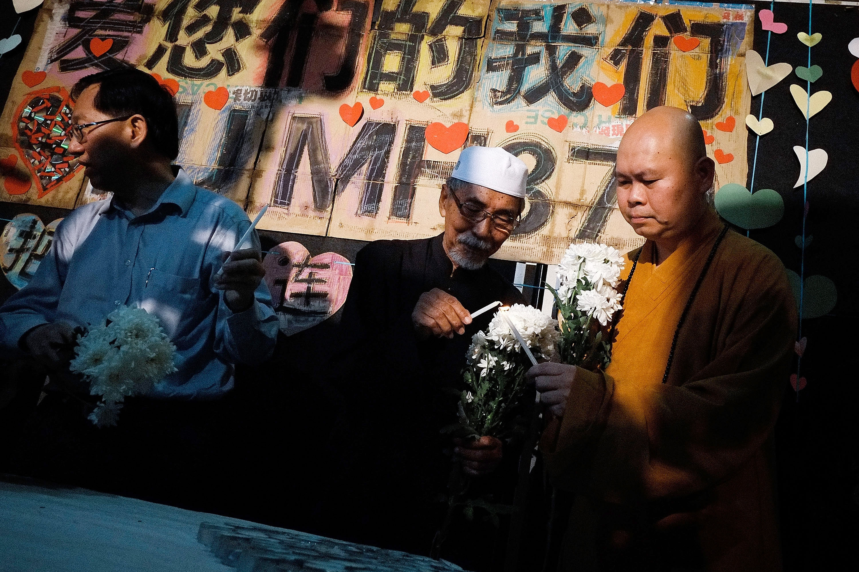 Representative from Muslim, Buddhist and Christian religions light candles during a vigil to remember the victim of the ill-fated Malaysia Airlines Flight 370 on Sunday in Kuala Lumpur, Malaysia.