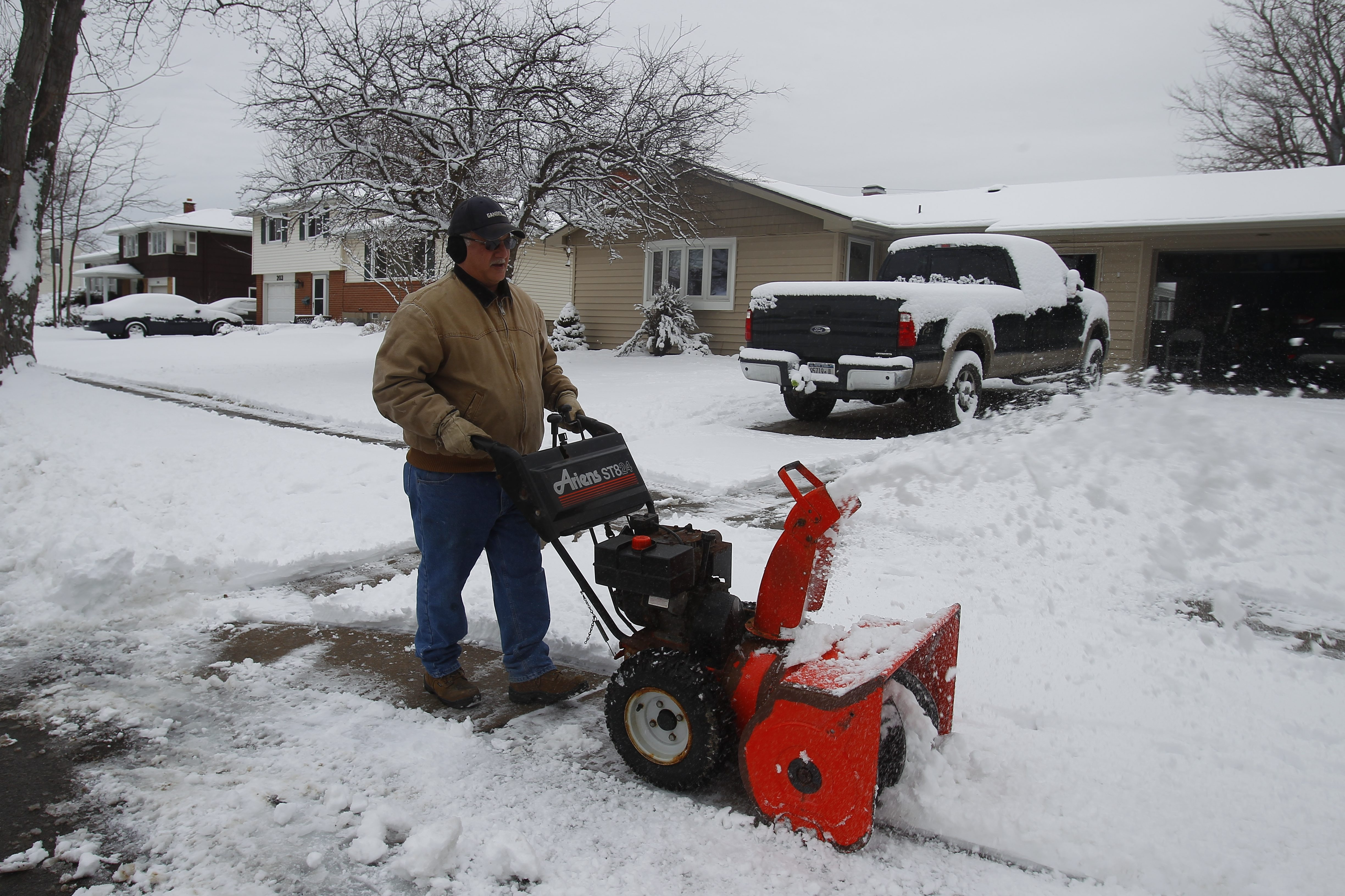 Peter Frank snowblows in the Town of Tonawanda Sunday as Western New Yorkers awoke to another snowfall despite the fact that winter officially ended March 20.