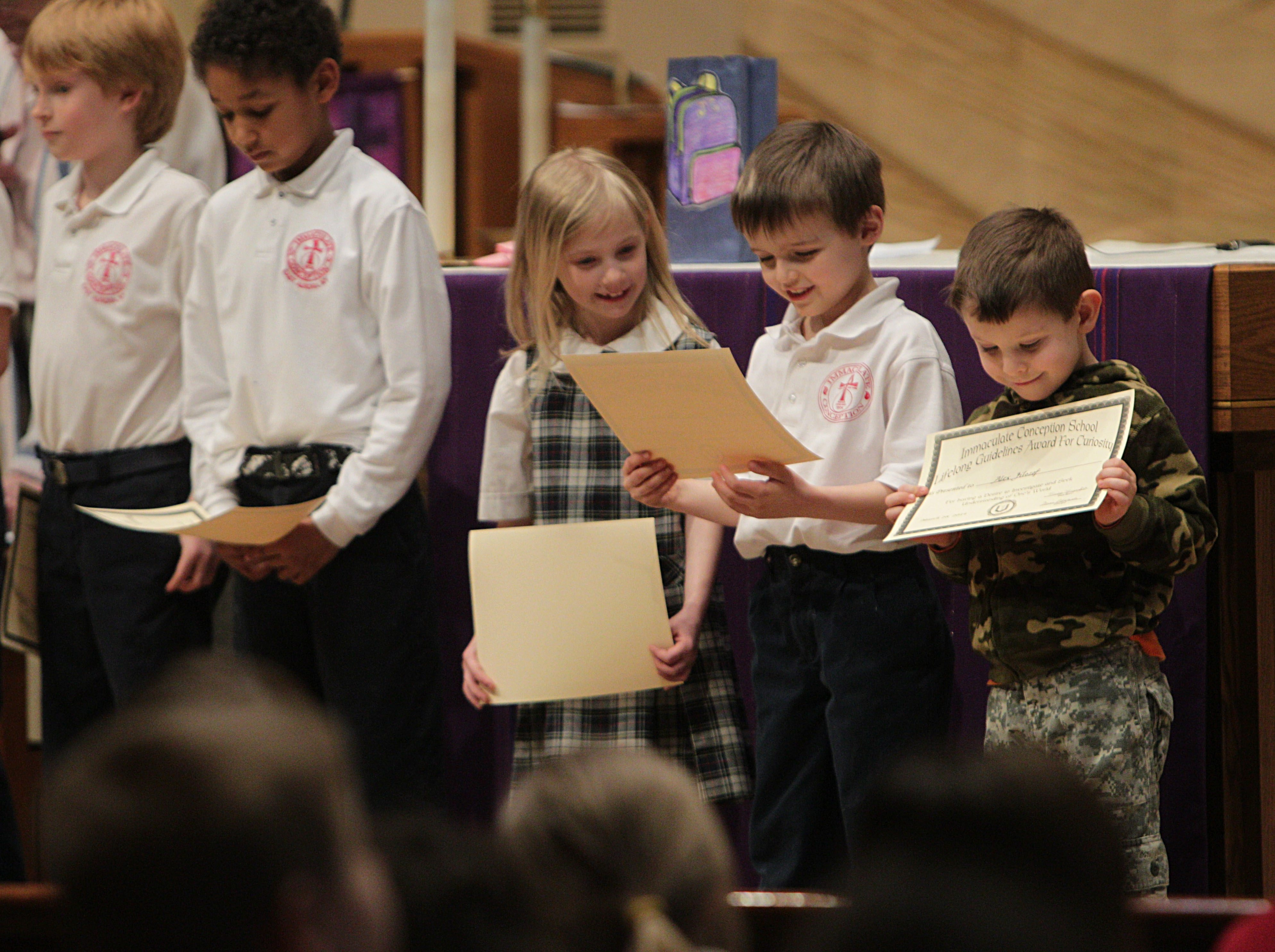 Immaculate Conception students Louisa Martin, third from left, Elias Pelletreau and Alex Filozof look at awards.