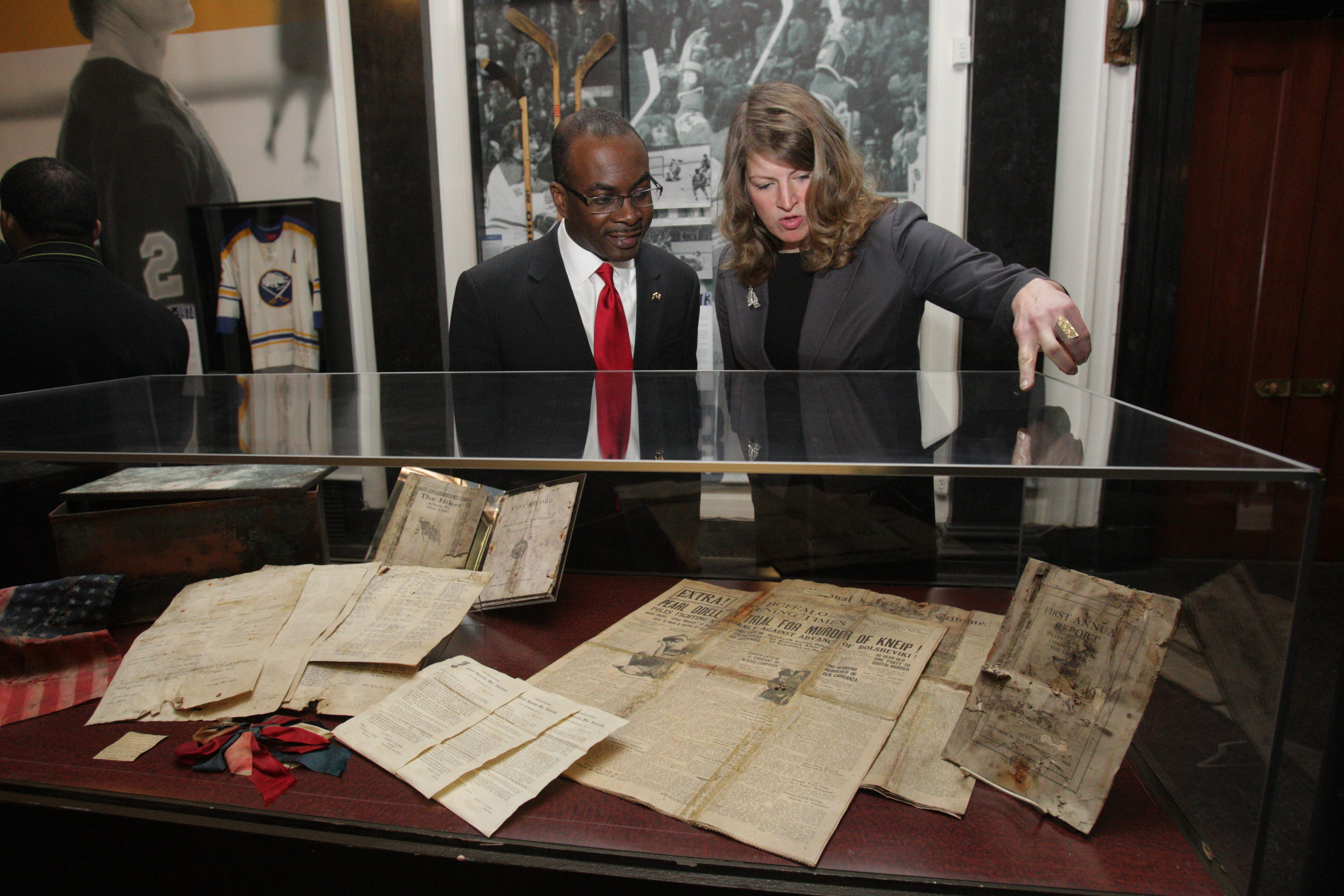 """Buffalo History Museum Executive Director Melissa Brown shows Mayor Byron W. Brown the contents of a time capsule Friday that was found last week at the base of """"The Hiker"""" statue at Main and Huron streets. See a photo gallery at BuffaloNews.com."""