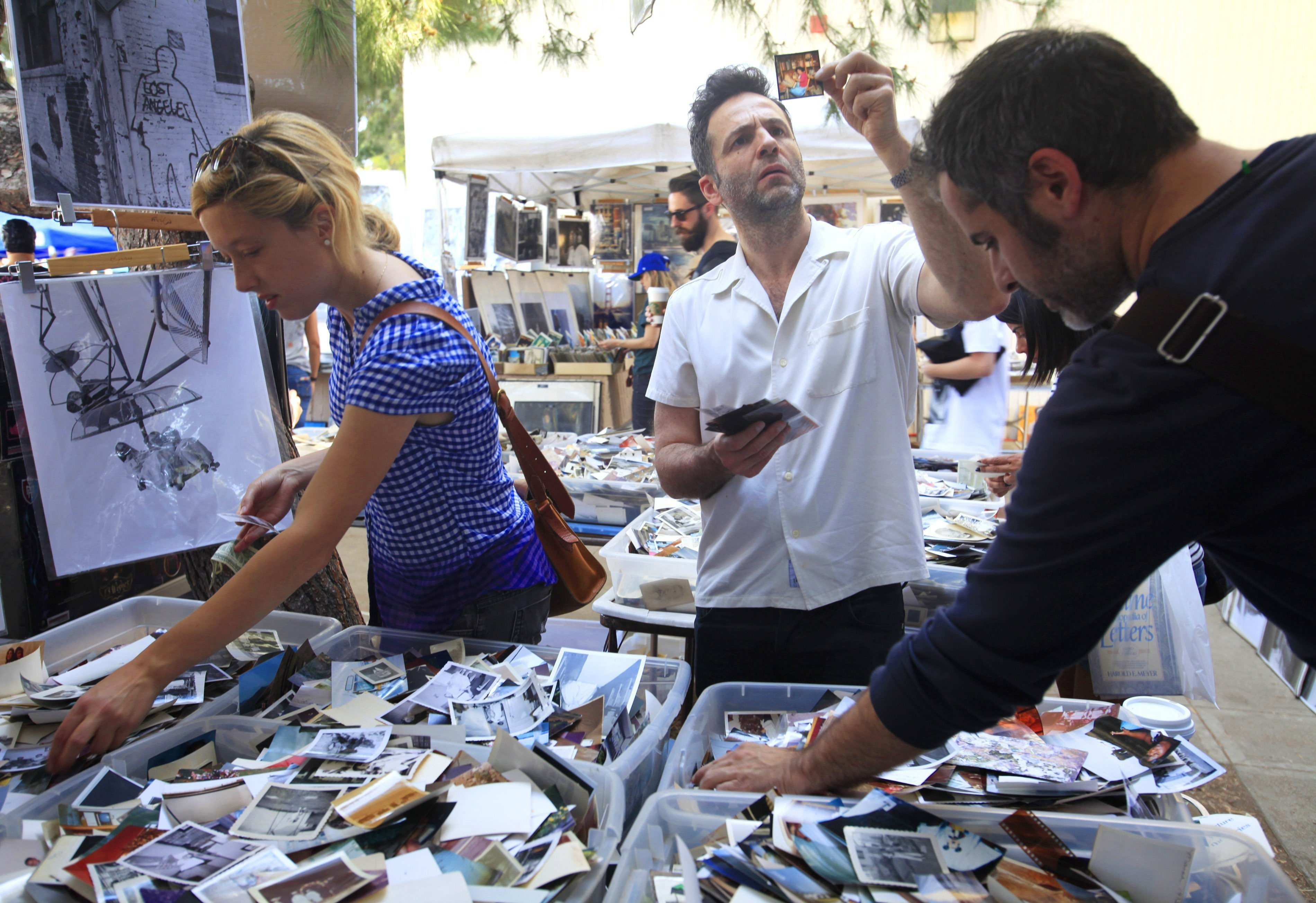 Shoppers are drawn to the bins of old photos for sale at the Melrose Trading Post outside Fairfax High School in Los Angeles.