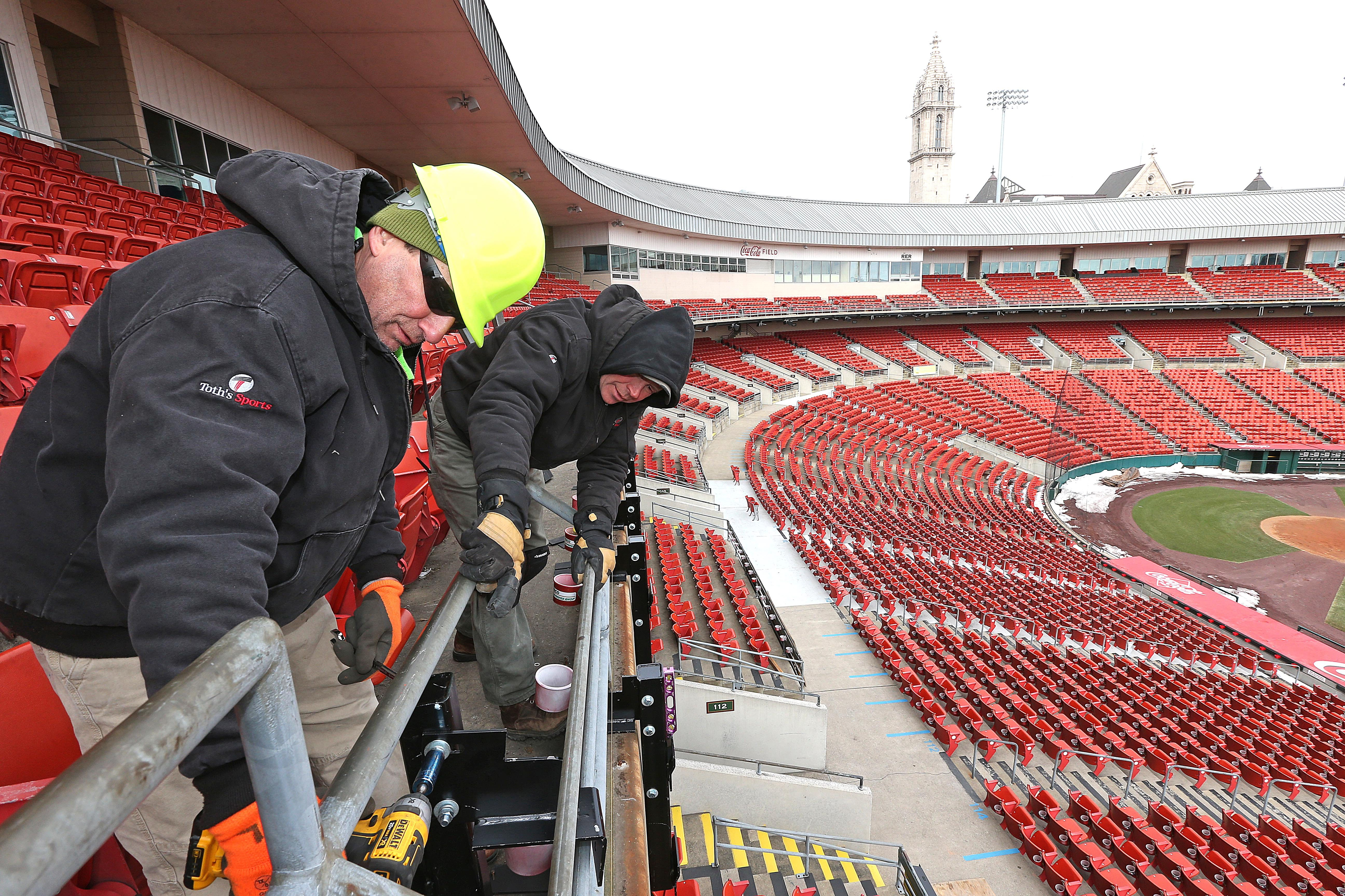 Tom Johnston, left, and Marty Ladd of Toth's Sports of Rochester install the support structures that will fasten the new LED light ribbon message boards on the front of the club-level balcony at Coca Cola Field.