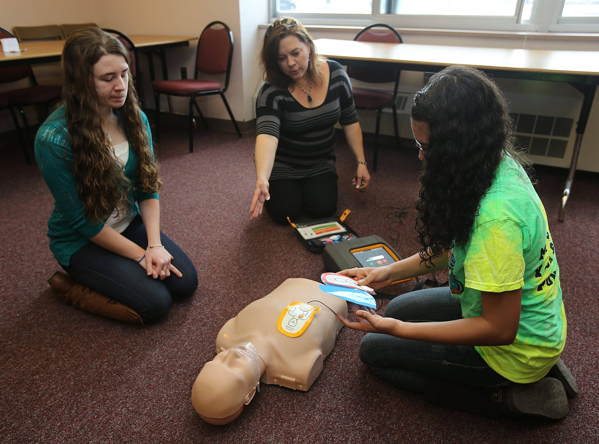 Annette Adamczak, who lost a daughter to heart attack, teaches Natalie McGill, left, and Antoinette Weatherspoon, 16, CPR techniques, using a Prestan CPR mannequin and an AED trainer, at Cheektowaga Central High School.
