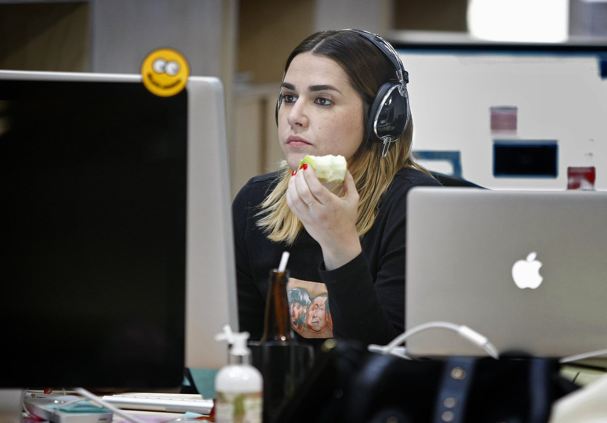 Kelly King munches on an apple while working at her desk at Stance, a designer sock company in San Clemente, Calif. The company provides healthy snacks for employees and has a gym, skateboard bowl, basketball court and table games.