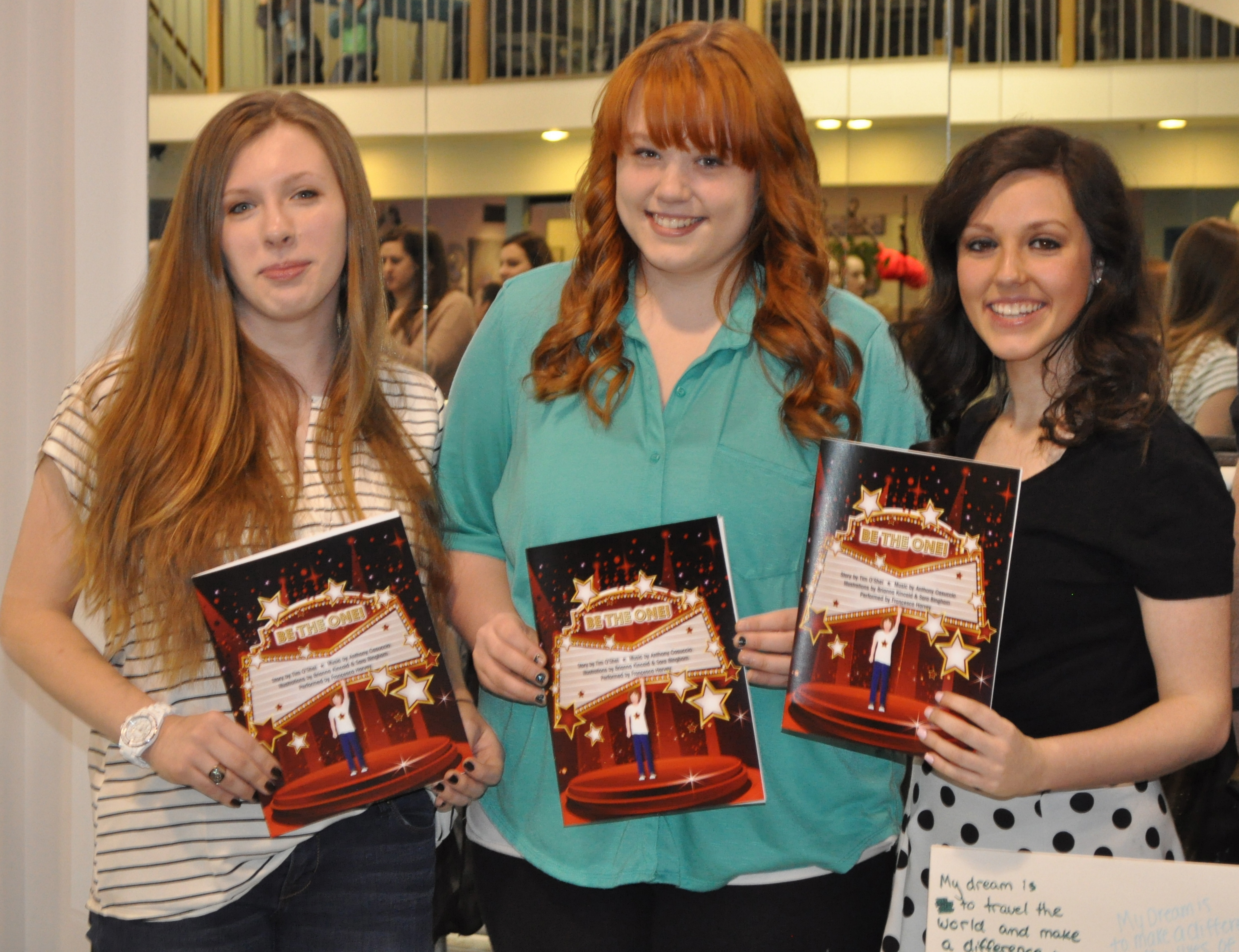 "Mount St. Mary Academy seniors Sara Bingham, Brianna Kincaid and Francesca Harvey with the ""Be the One!"" coloring book."