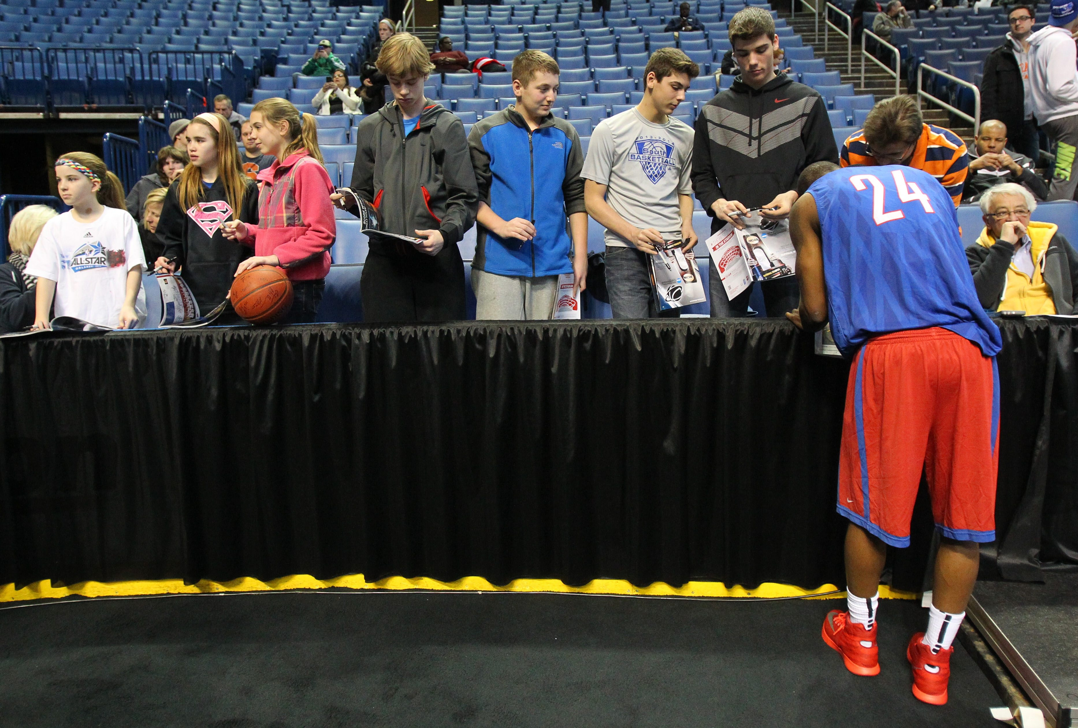 Dayton's Jordan Sibert, who transferred from Ohio State, signs autographs for fans after practice.