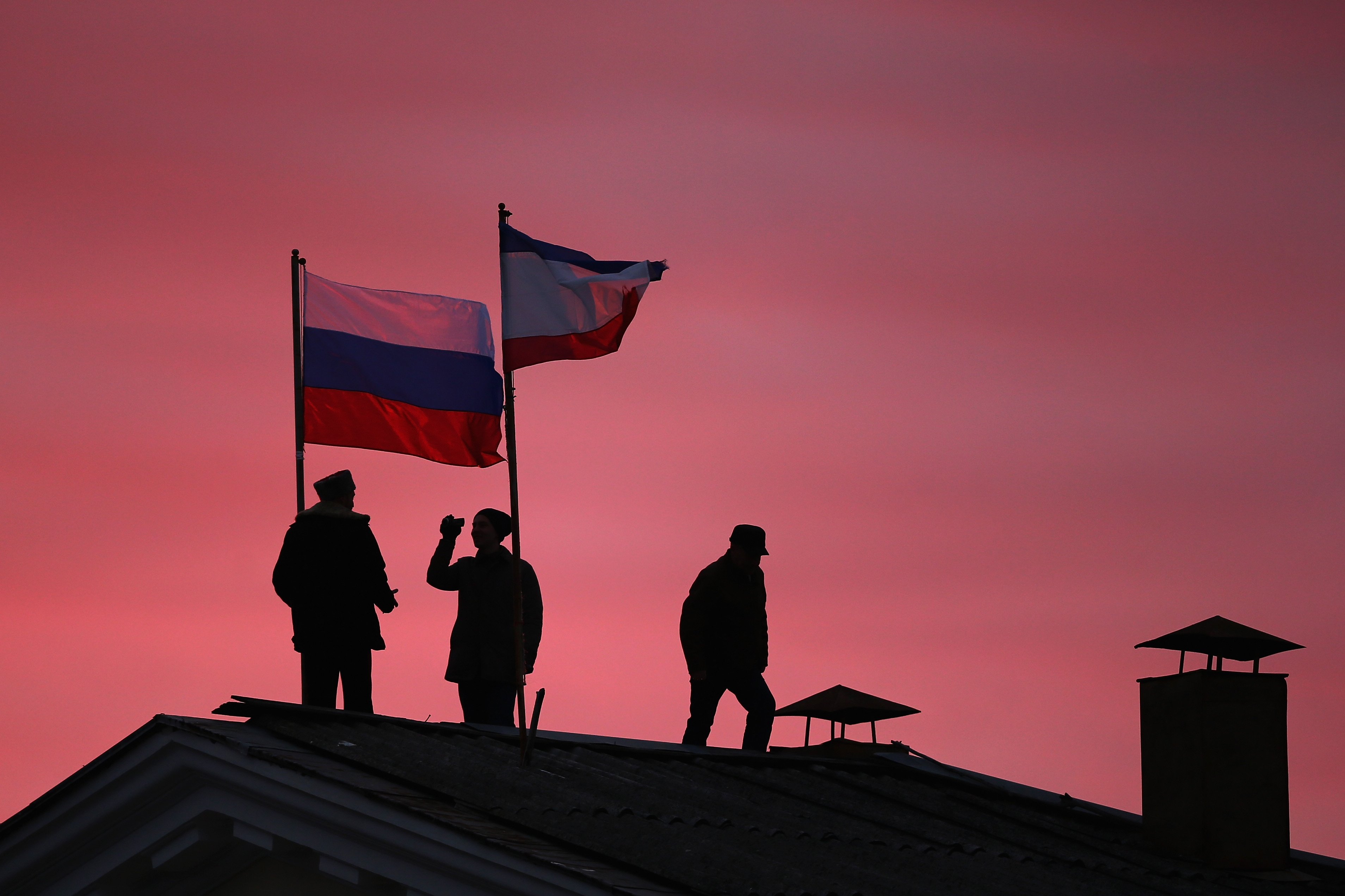 Cossack men on Monday install a Russian flag and a Crimean flag on the roof of the City Hall building in Bakhchysarai, central Crimea, Ukraine.