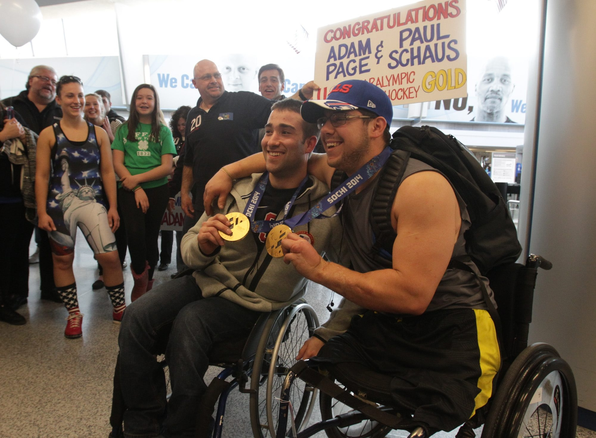 U.S. gold medal-winning sled hockey Paralympians Adam Page, left, and Paul Schaus receive a hero's welcome Monday after arriving at the Buffalo Niagara Airport in Cheektowaga.