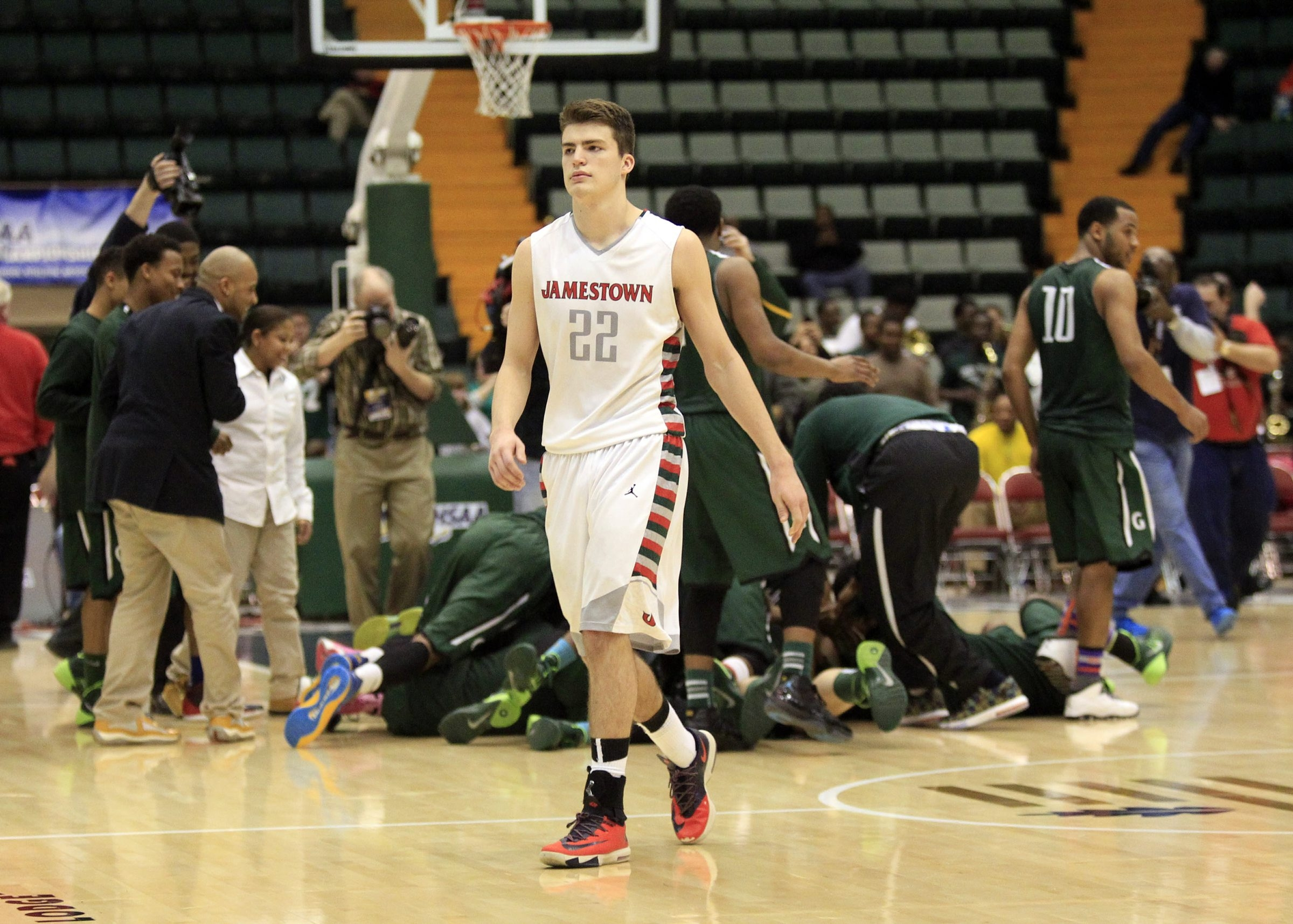 Stephen Carlson walks off as Green Tech players celebrate in the background after the Eagles' 54-49 win in the state Class AA title game.