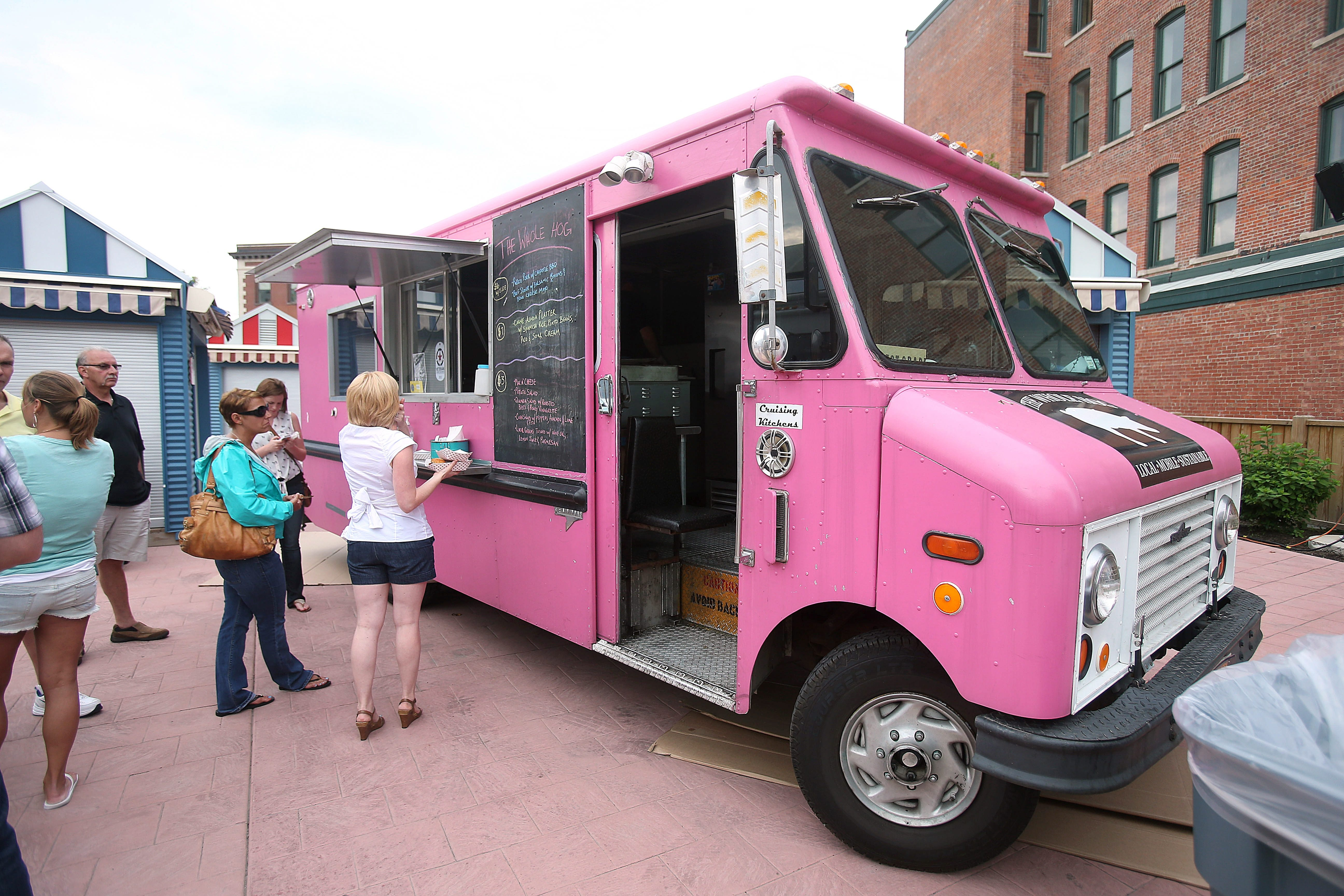 Patrons order from the Whole Hog food truck June 25, 2013.