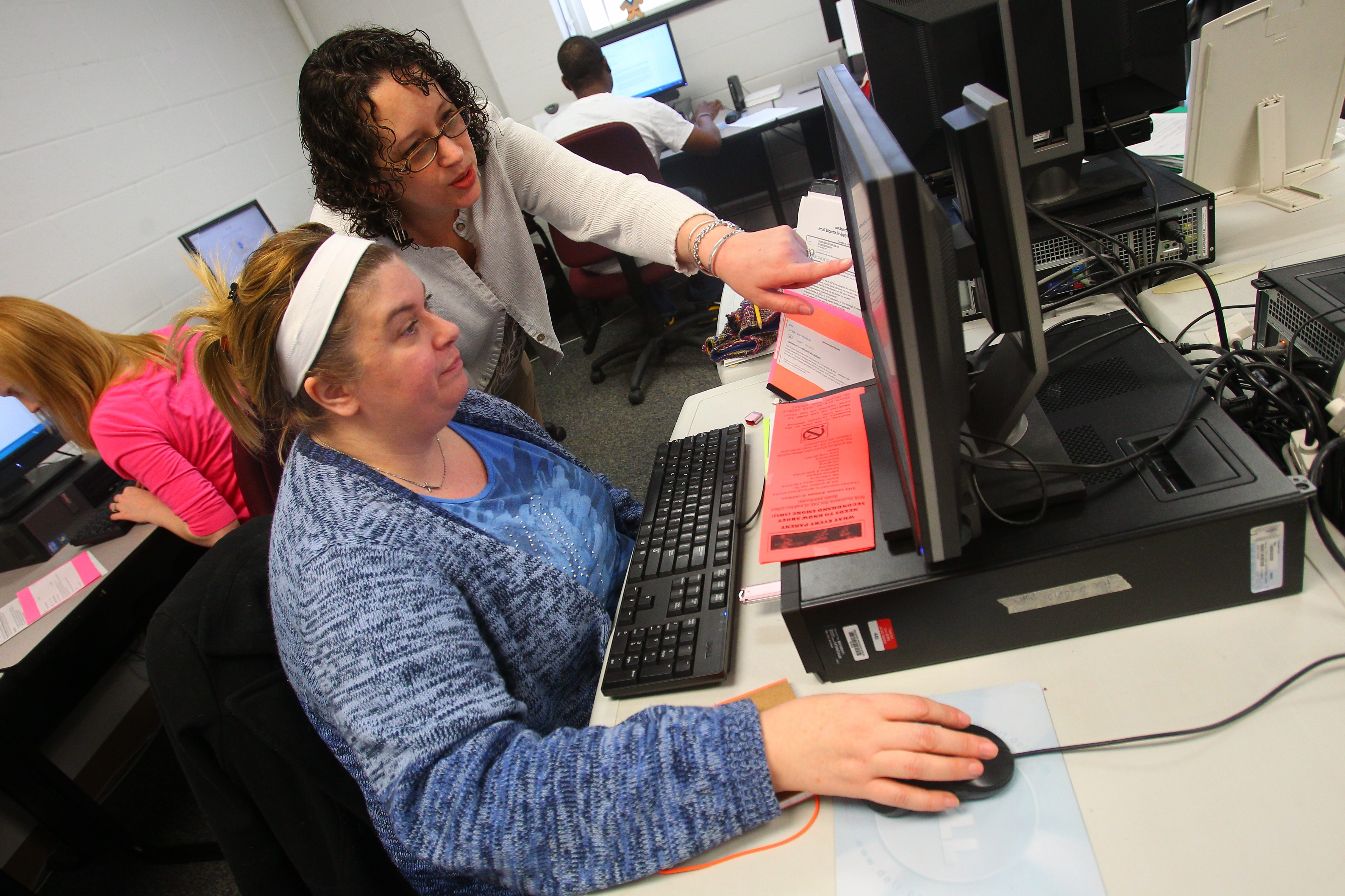 Jessica Bush, a member of the Orleans-Niagara BOCES staff, offers pointers on sending résumés by email to Kristen Frain, who recently lost her job, during adult literacy class at Christ Community Church in Lockport.