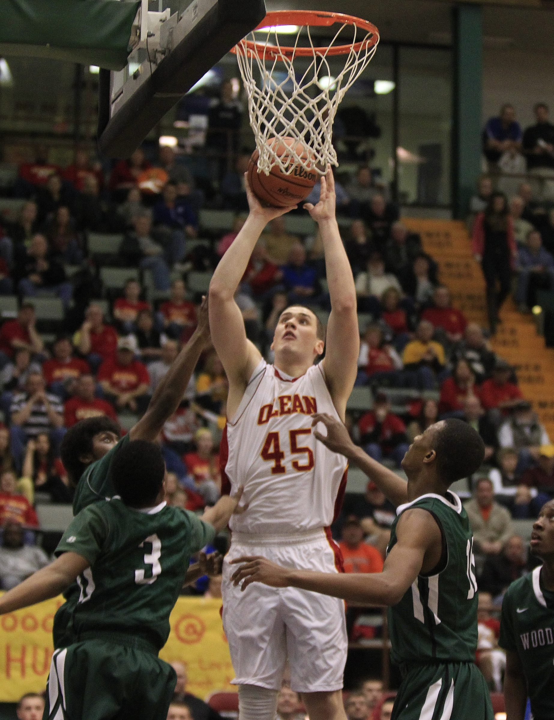 Olean's Sam Eckstrom shoots over three Woodlands players in Friday night's game.