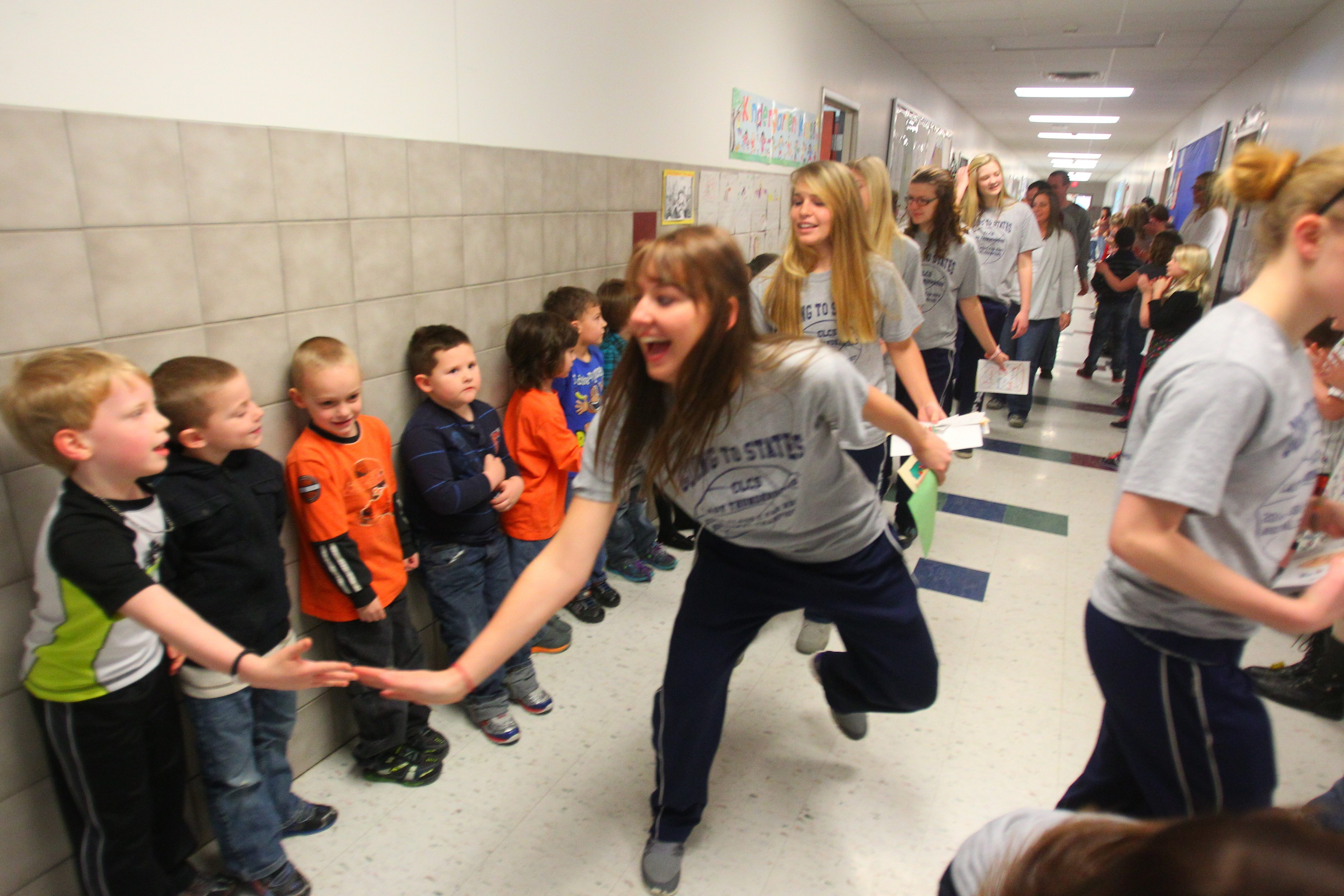 Ashley Moulton of the Chautauqua Lake basketball team slaps hands with a young well-wisher after a pep rally on Friday at the school.