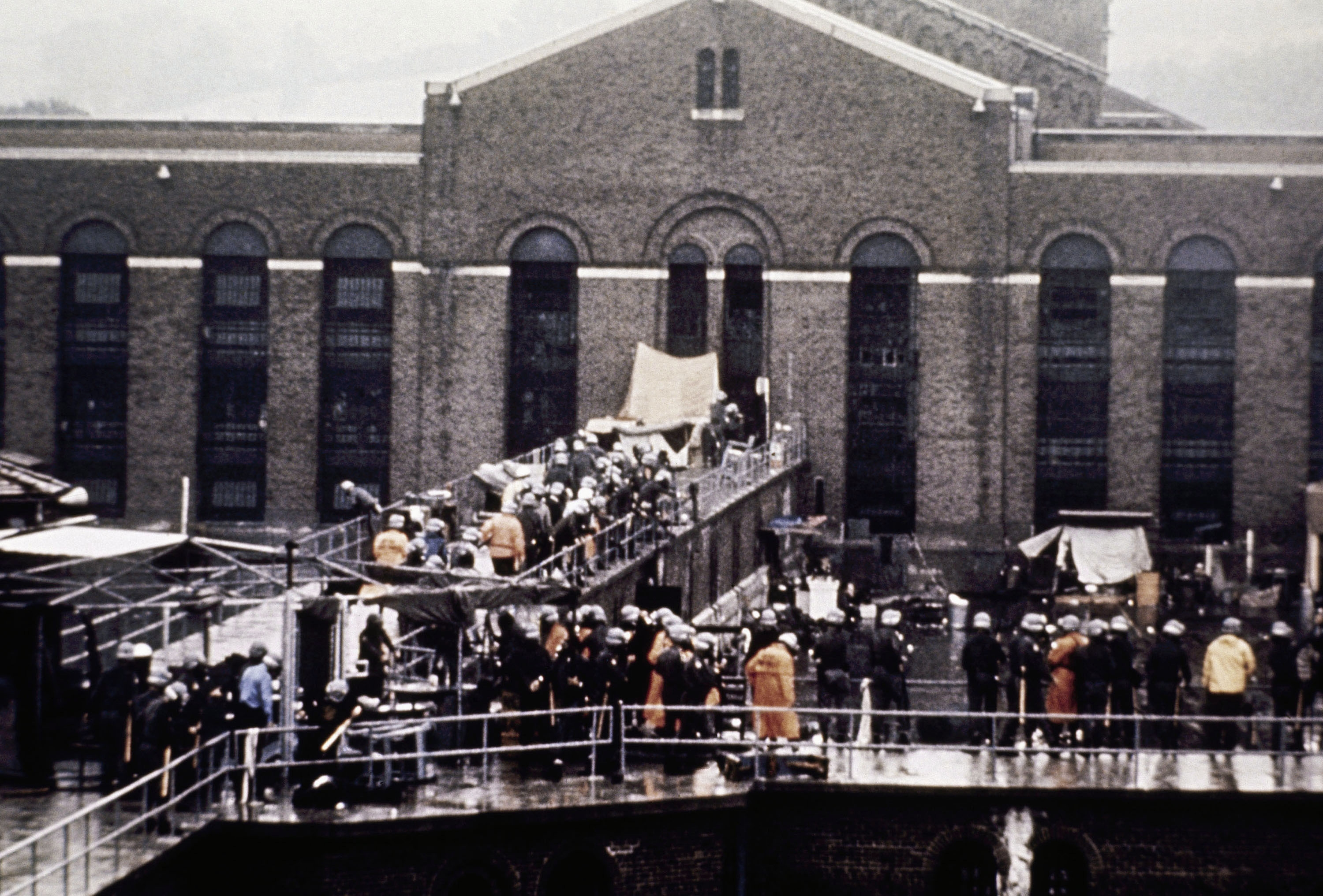In this Sept. 13, 1971, file photo, prison guards and  New York State troopers gather outside Attica State Prison after retaking it from inmates who rioted and held the prison for five days, in Attica.