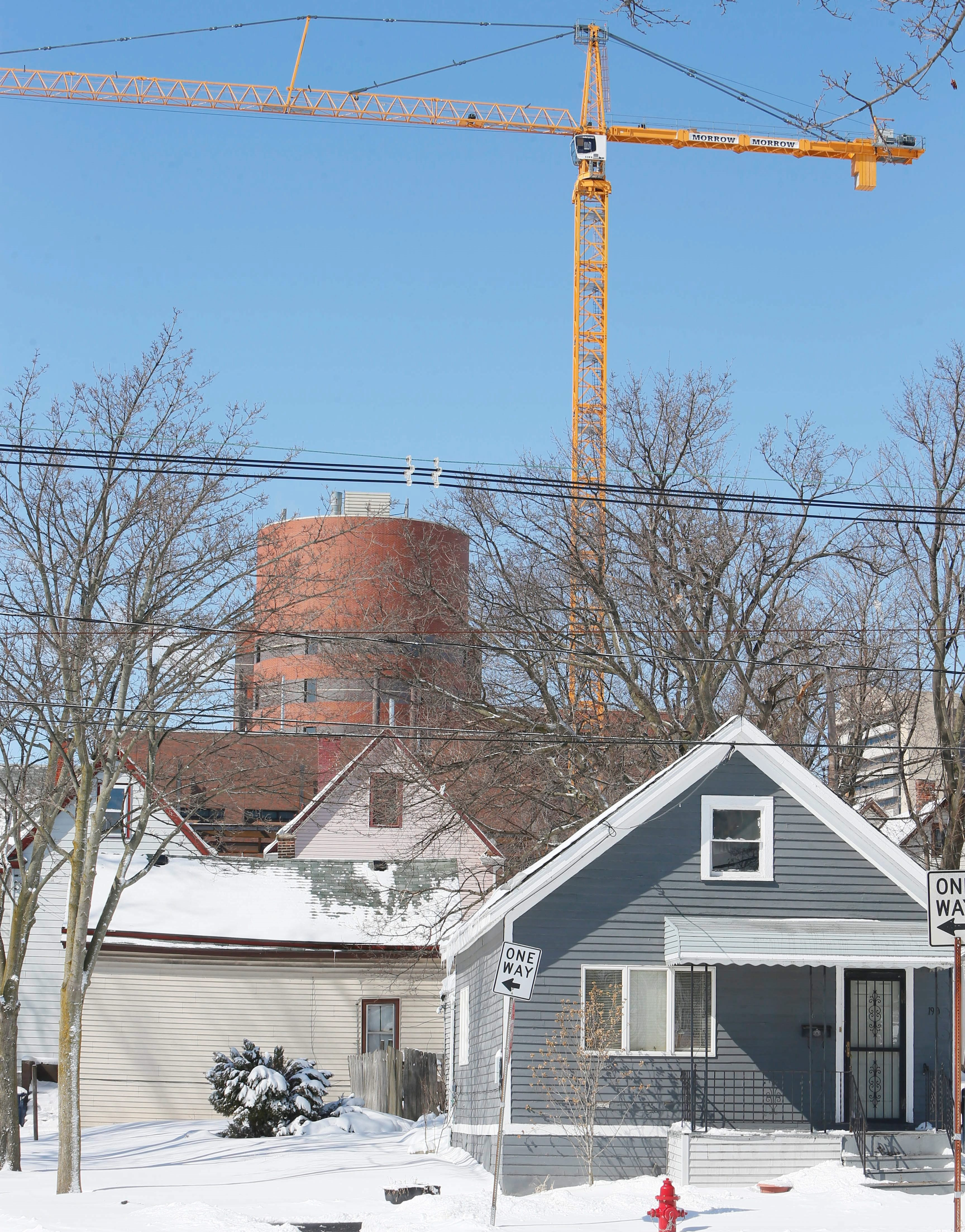 In the shadow of a tower crane at the Medical Campus, a house on Mulberry Street is among those with doubts looming over impact of development on Fruit Belt residents' property values.