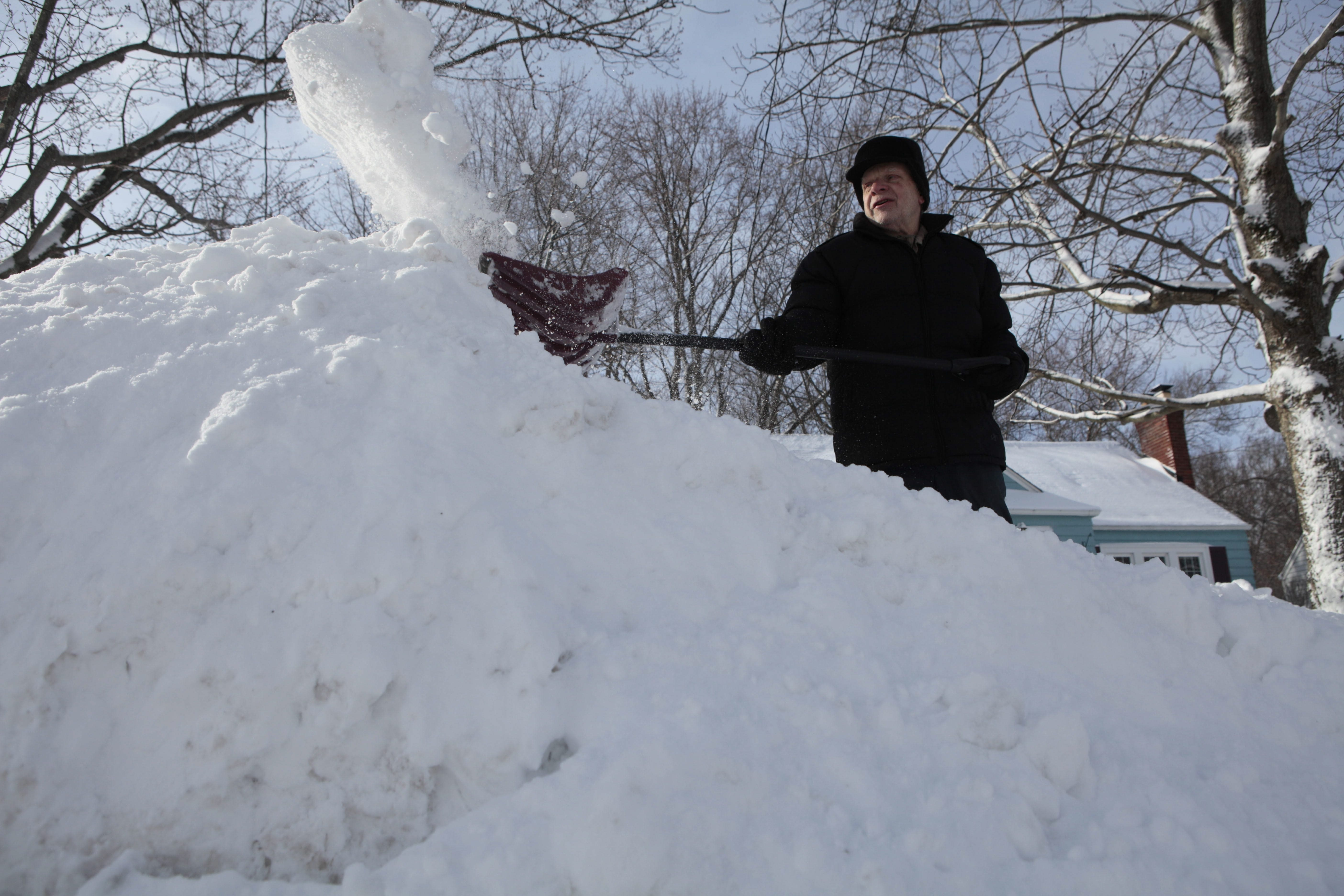 Stuart Meyer shovels out his driveway on Huntington Court in Hamburg today.  (Derek Gee/Buffalo News)