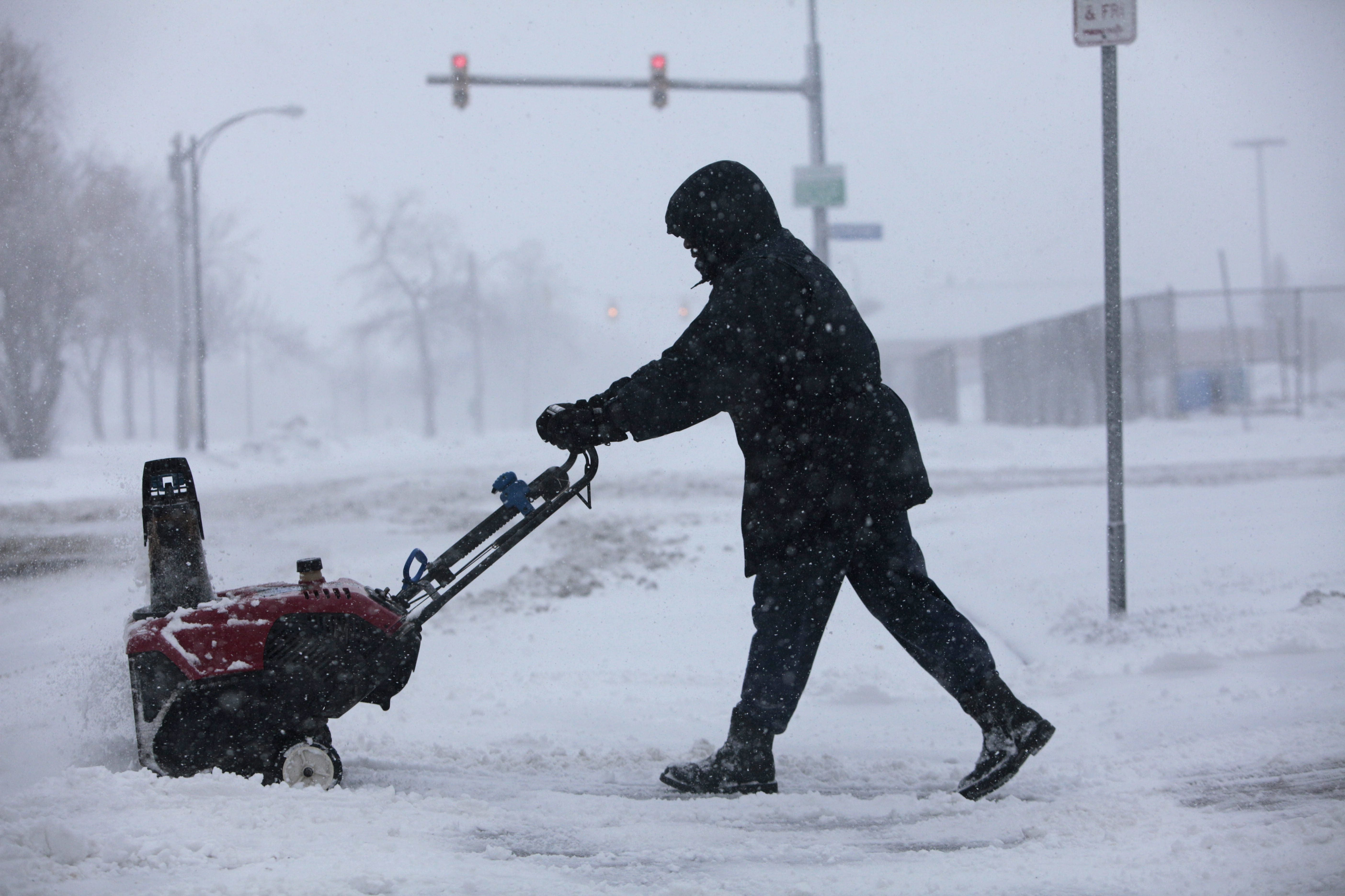 """Gary Alexander uses a snowblower to clear out his driveway and sidewalk on Pine Street.  """"If we're going to get 12 to 18 inches, you can't let it build up,"""" he said."""