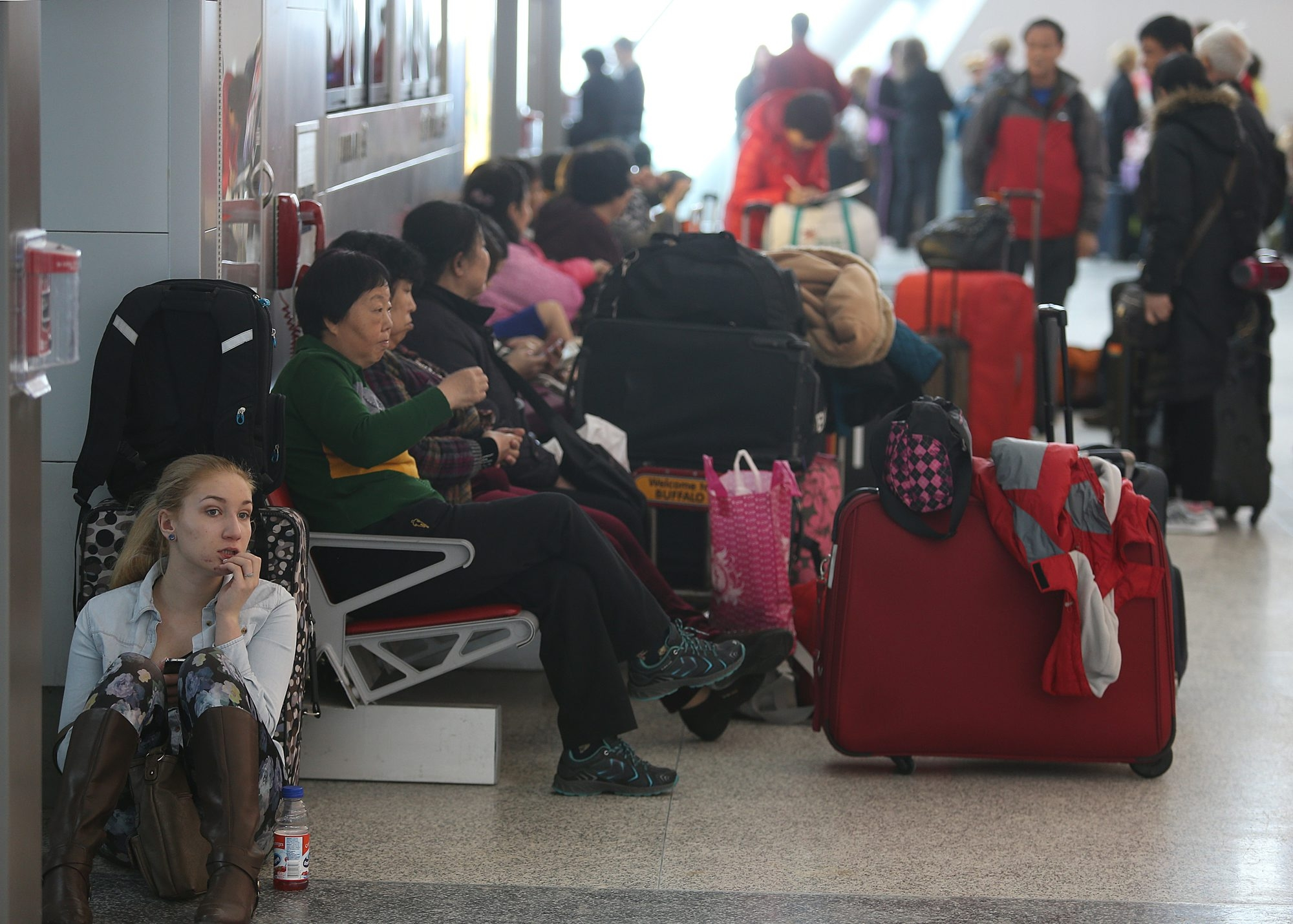 Passengers wait in the terminal after most flights were canceled at Buffalo Niagara International Airport.