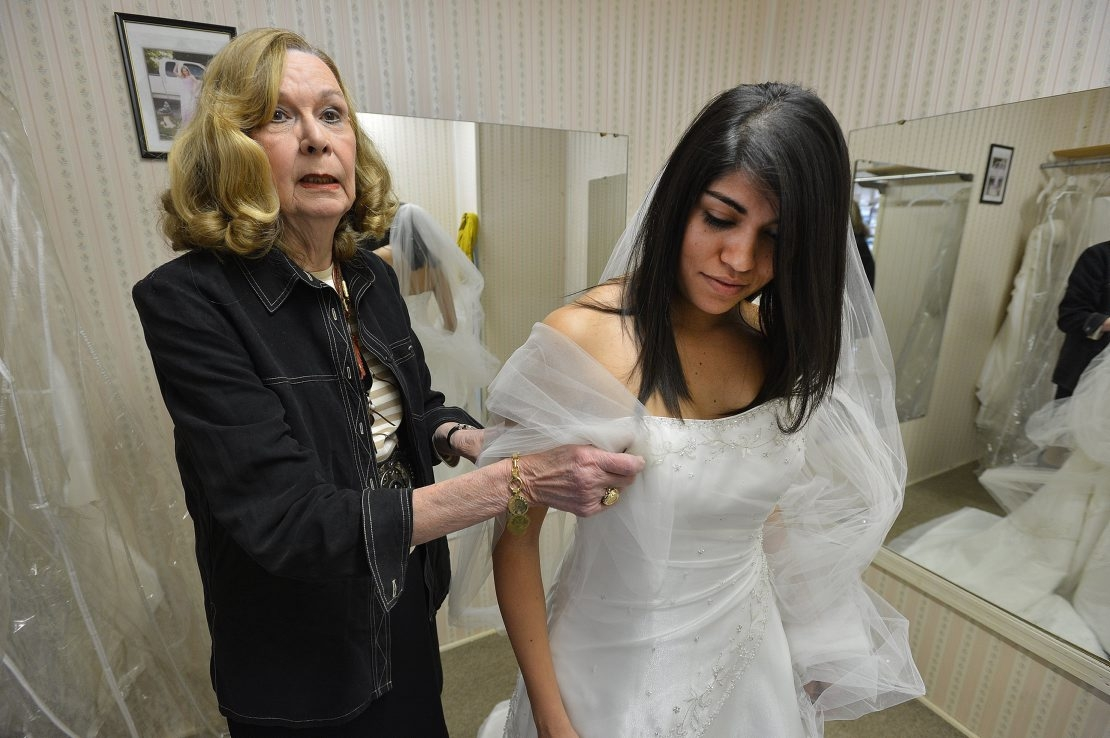 Betty Ziegler Mims, left, helps Susan Castillo with her decision on picking the perfect wedding dress. Mims is closing her bridal shop in Charlotte, N.C., after 50 years of helping brides find affordable dresses.