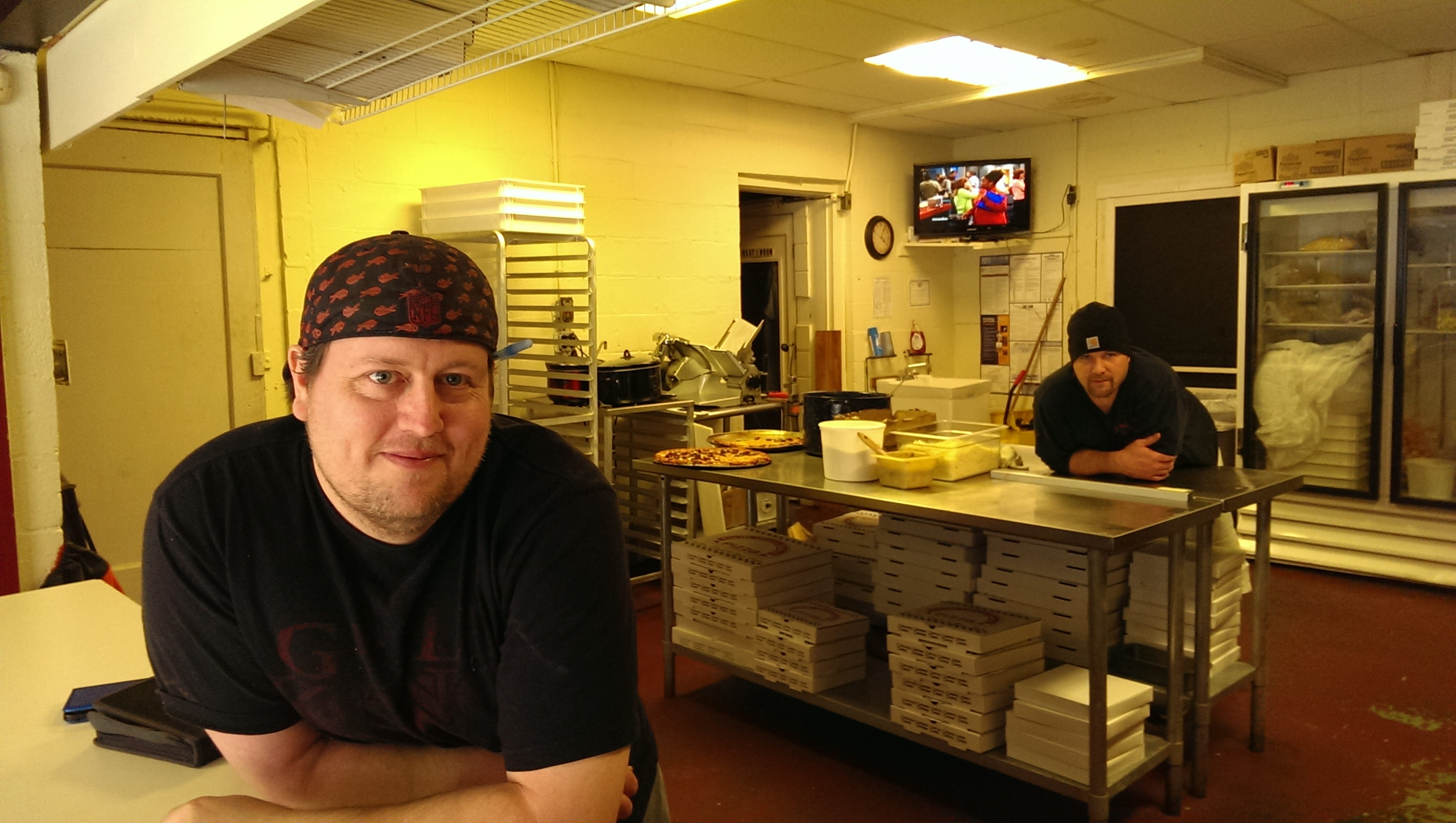 Pizza delivery man Greg Harris, left, and Fat Man Pizza co-owner Brad Neupert stayed open during the winter storm.