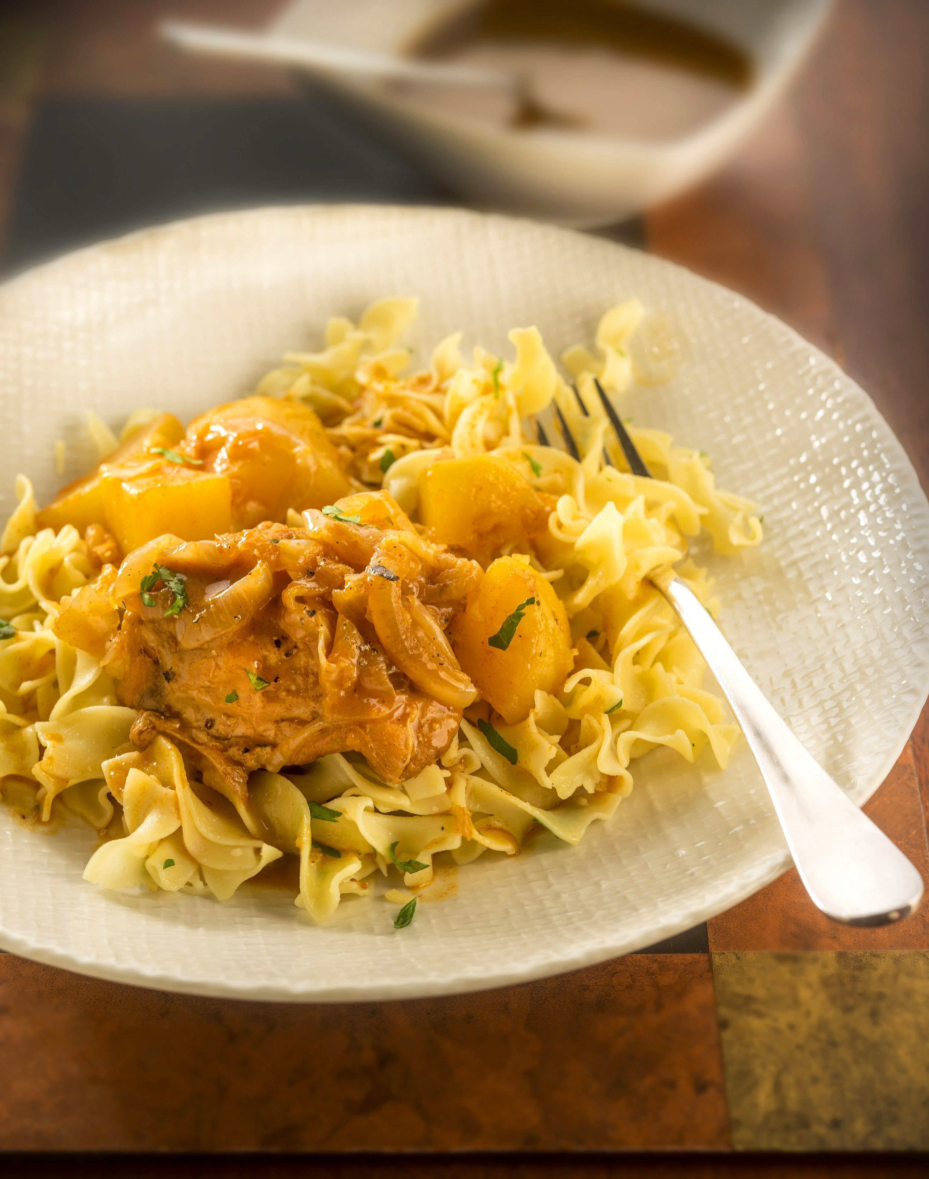 Hungarian paprika is a key ingredient in chicken goulash with potatoes, shown above with egg noodles.