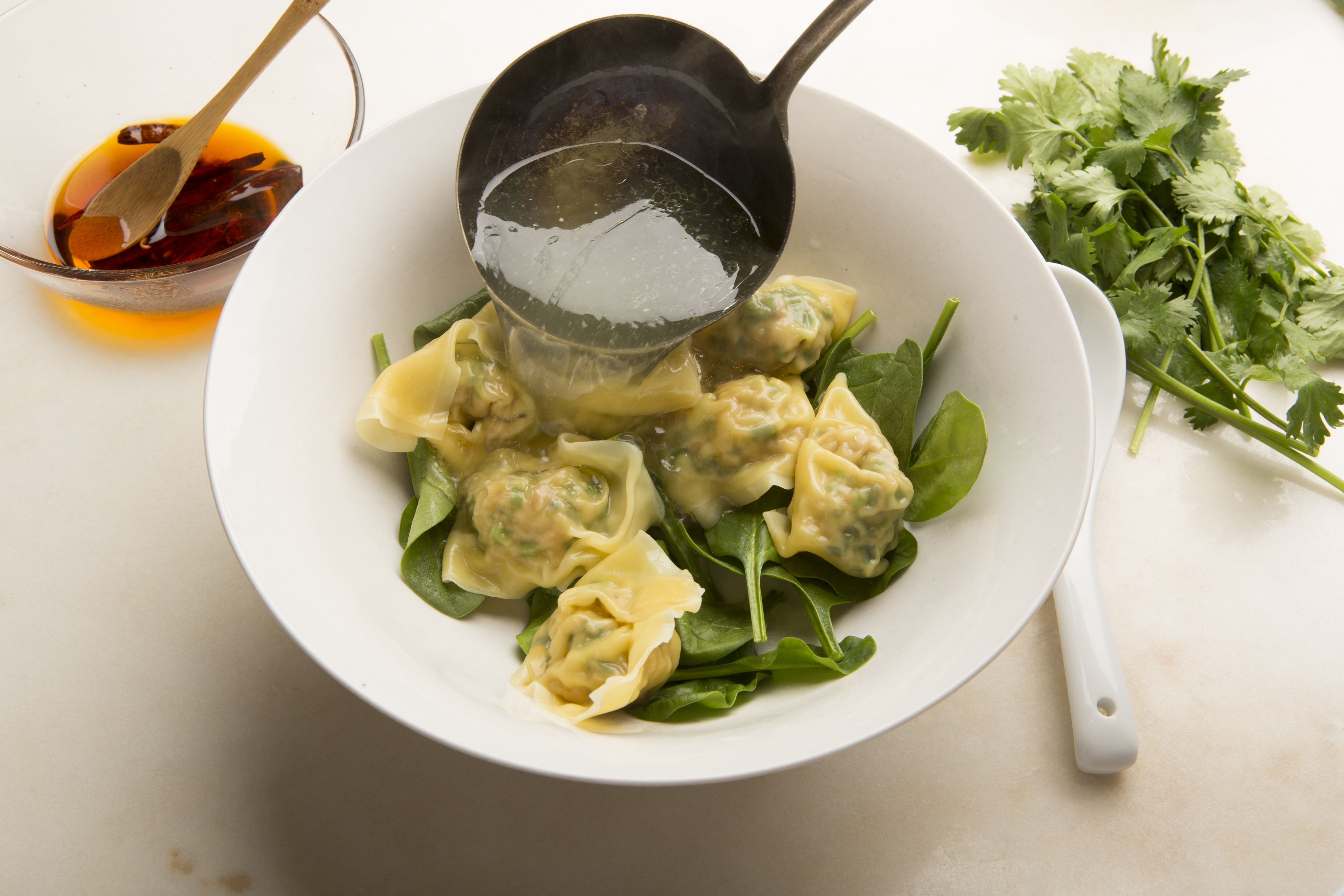 Serve homemade won tons with a clear broth, spinach, cilantro and hot pepper oil.