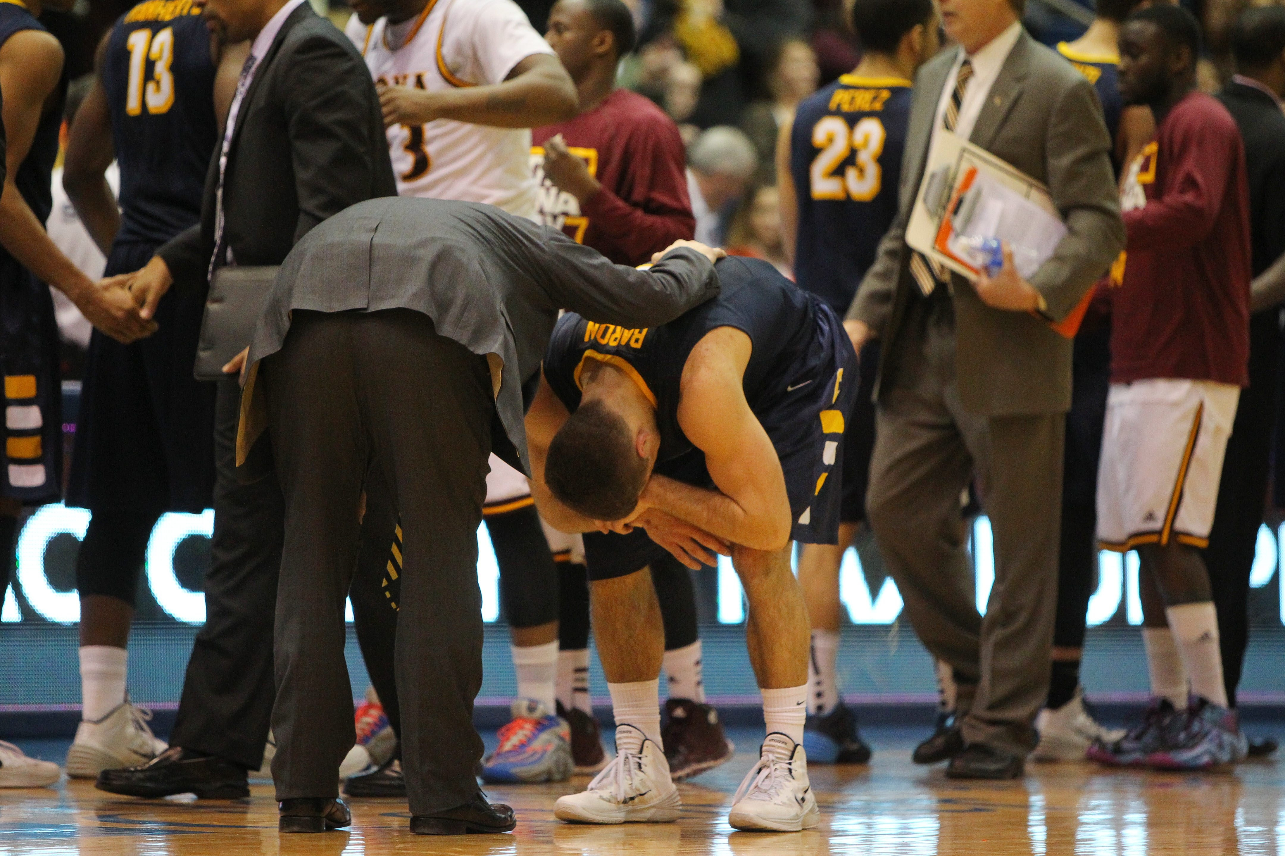 Canisius' Billy Baron is consoled by team manager Cory Macchioni after losing to Iona in Sunday's MAAC semifinal.