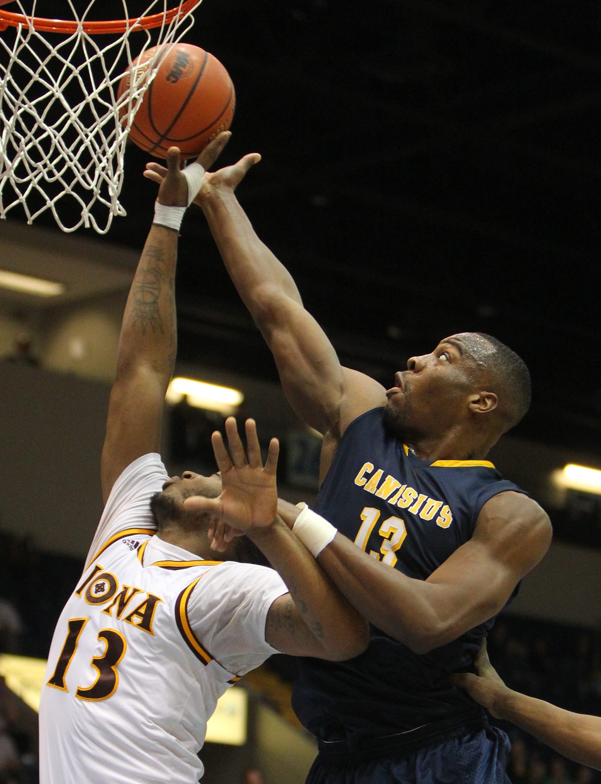 Canisius' Chris Manhertz (right) reaches for a rebound with Iona's David Laury.