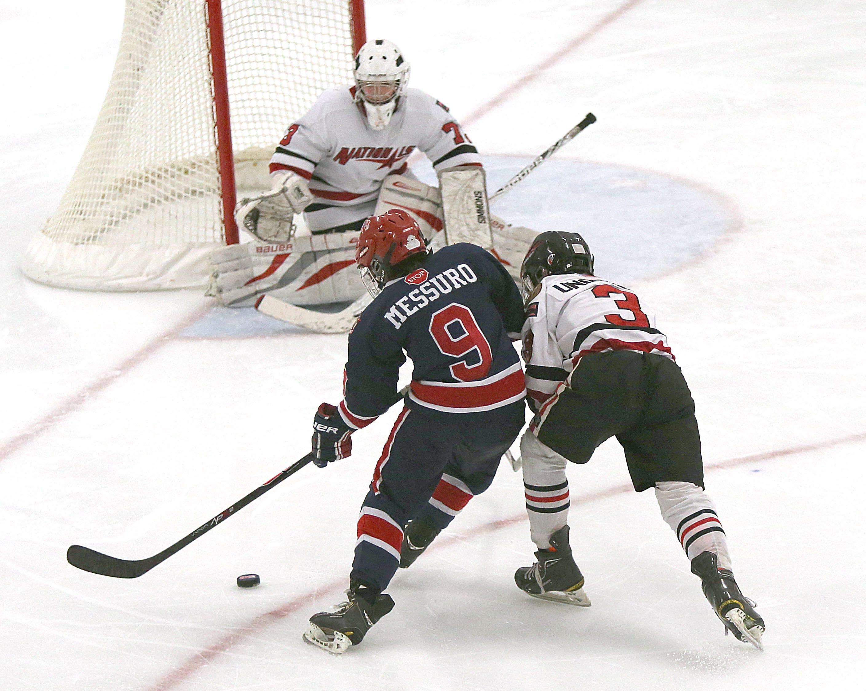 Buffalo Regals 12-under team member Nick Messuro (9) goes to the net against Syracuse goalie Michael Lenhart and defensman Logan Ungleich.