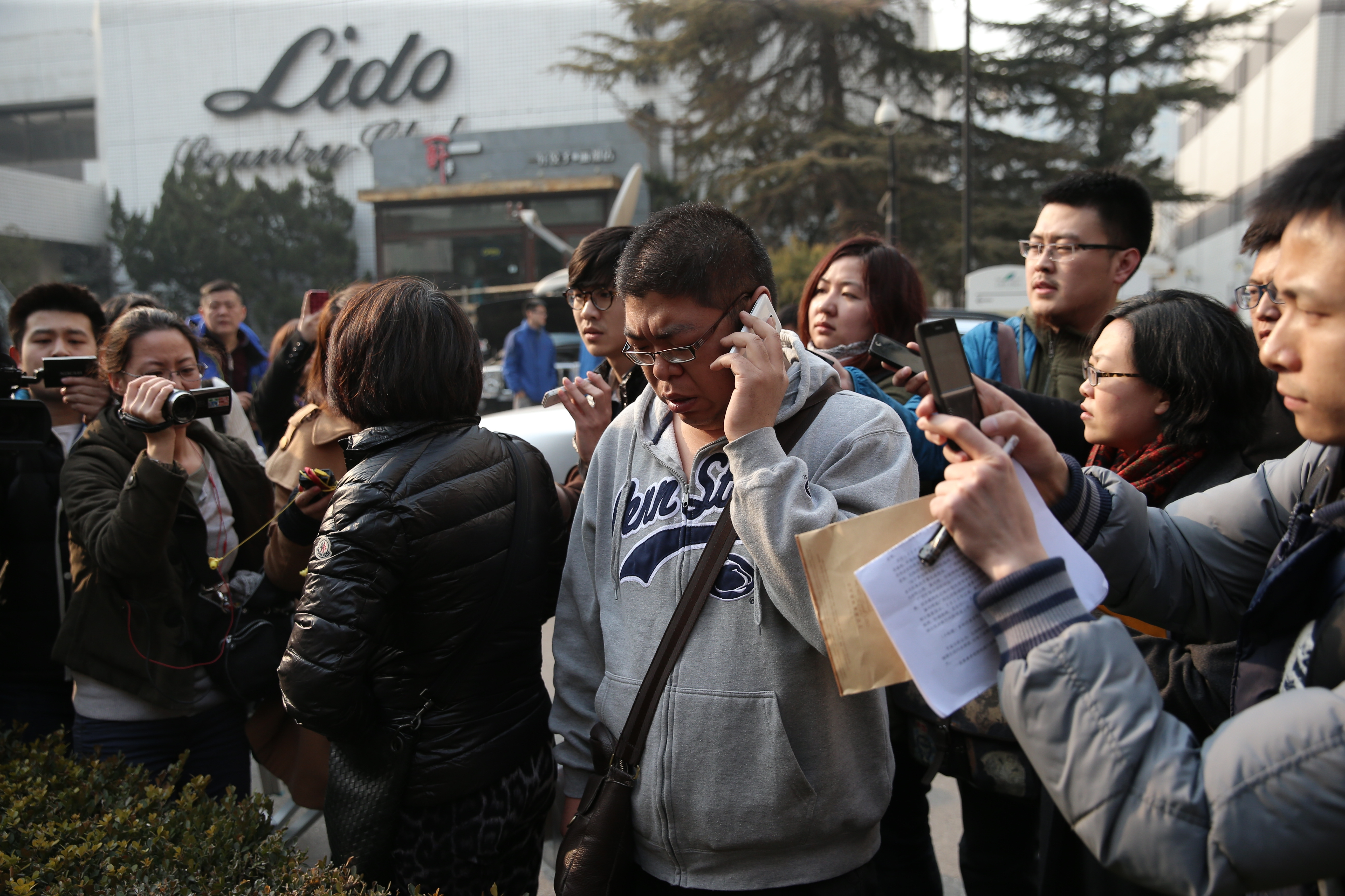 A relative of a passenger onboard Malaysia Airlines flight MH370 makes a call at Lidu Hotel on Saturday in Beijing, China. The flight from Kuala Lumpur to Beijing was reported missing after the crew failed to check in as scheduled while flying over the sea between Malaysia and Ho Chi Minh City in Vietnam, according to published reports.