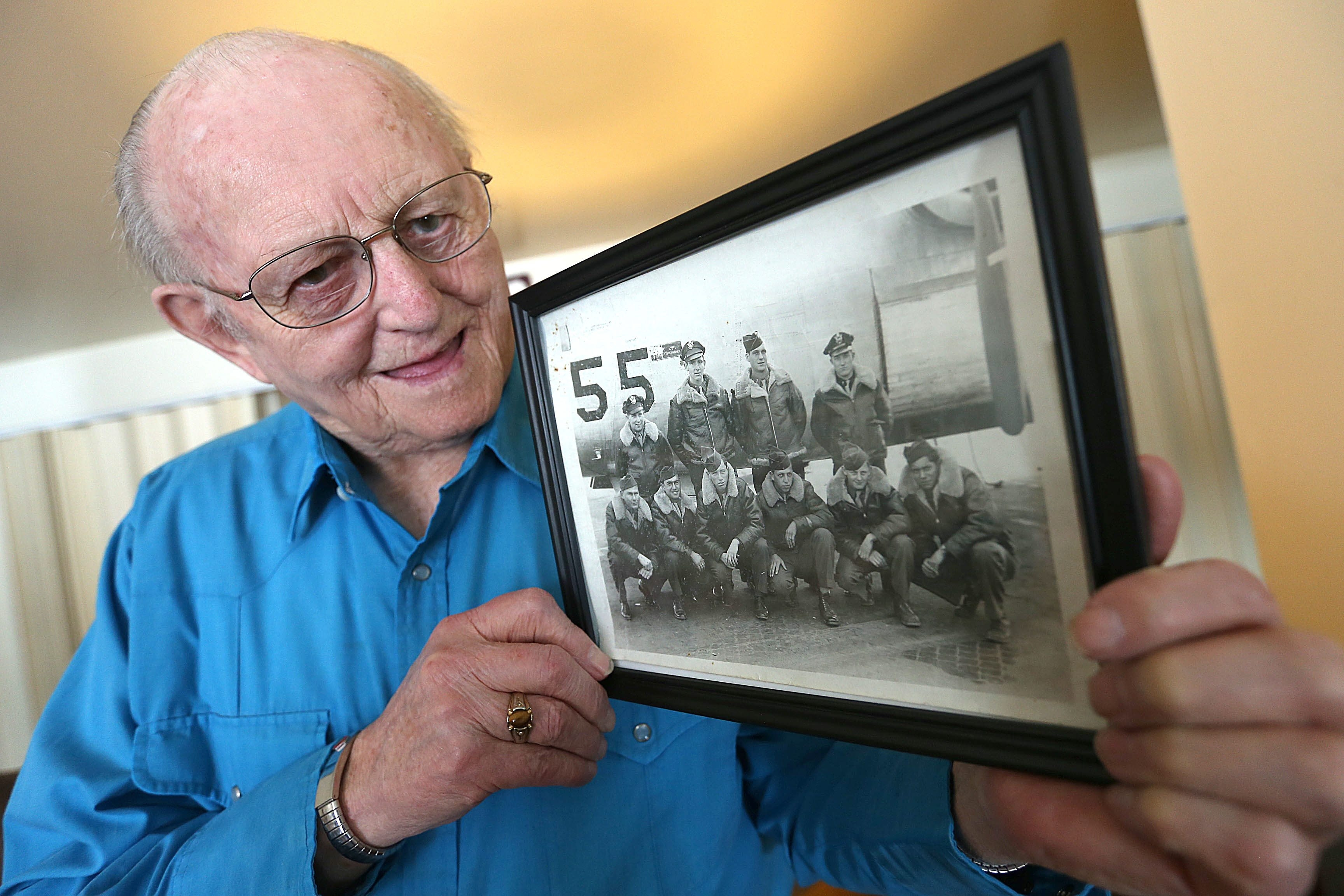 Paul E. Allan, at home in Springville with photo of his bomber crew, had flown above Hiroshima and Nagasaki in weeks before the atomic bombs were dropped on Japan.