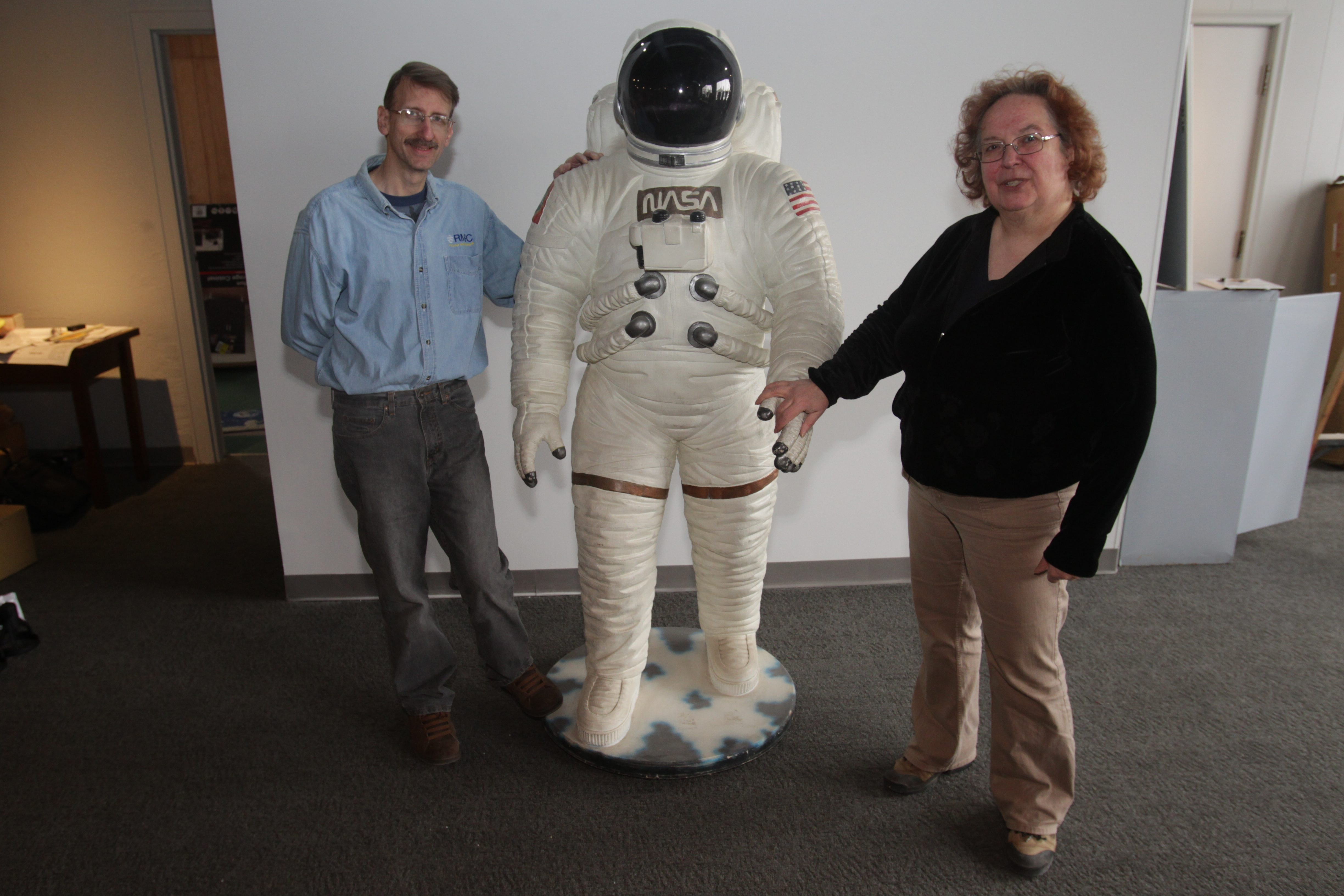 Kathy Michaels, director of soon-to-open Challenger Learning Center at Harrison Place in Lockport, and Paul Krupinski, who runs the planetarium, ensure that details of imitation astronaut Biff are authentic for display at 5,500-square-foot site.