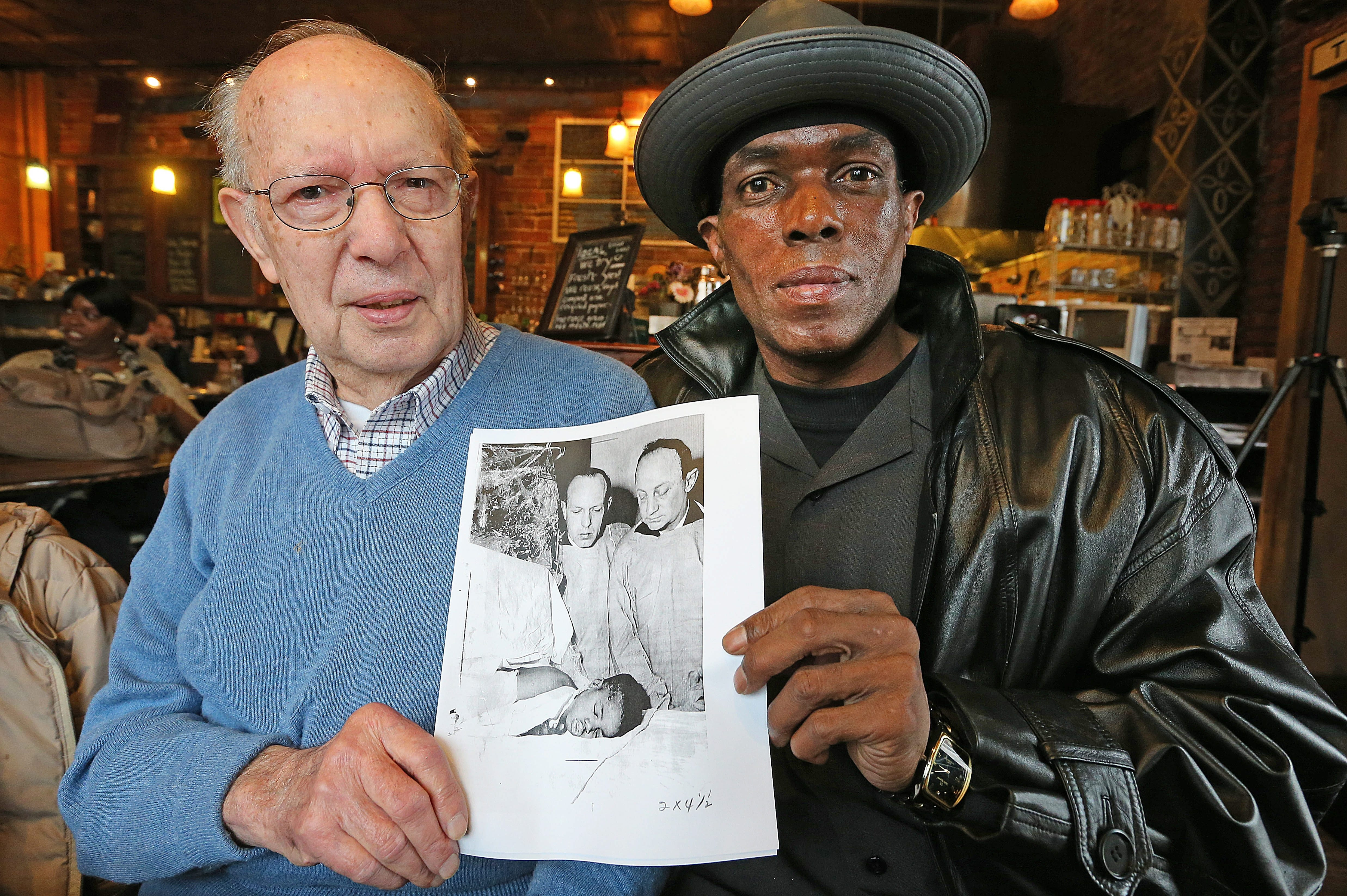 Patrick Weatherspoon, right, meets retired firefighter Vincent Fildes, left, at Sweetness 7 Cafe on Grant St. on Friday, Feb. 21, 2014.  Fildes rescued Weatherspoon from a house fire in 1968 and this is the first time they've reunited since the fire that took his sister at 397 Sherman St in Buffalo. They were looking at a photo by Buffalo News staff photographer Bill Dyviniak of the next day visit at the hospital where the youngster was recovering.   (Robert Kirkham/Buffalo News)