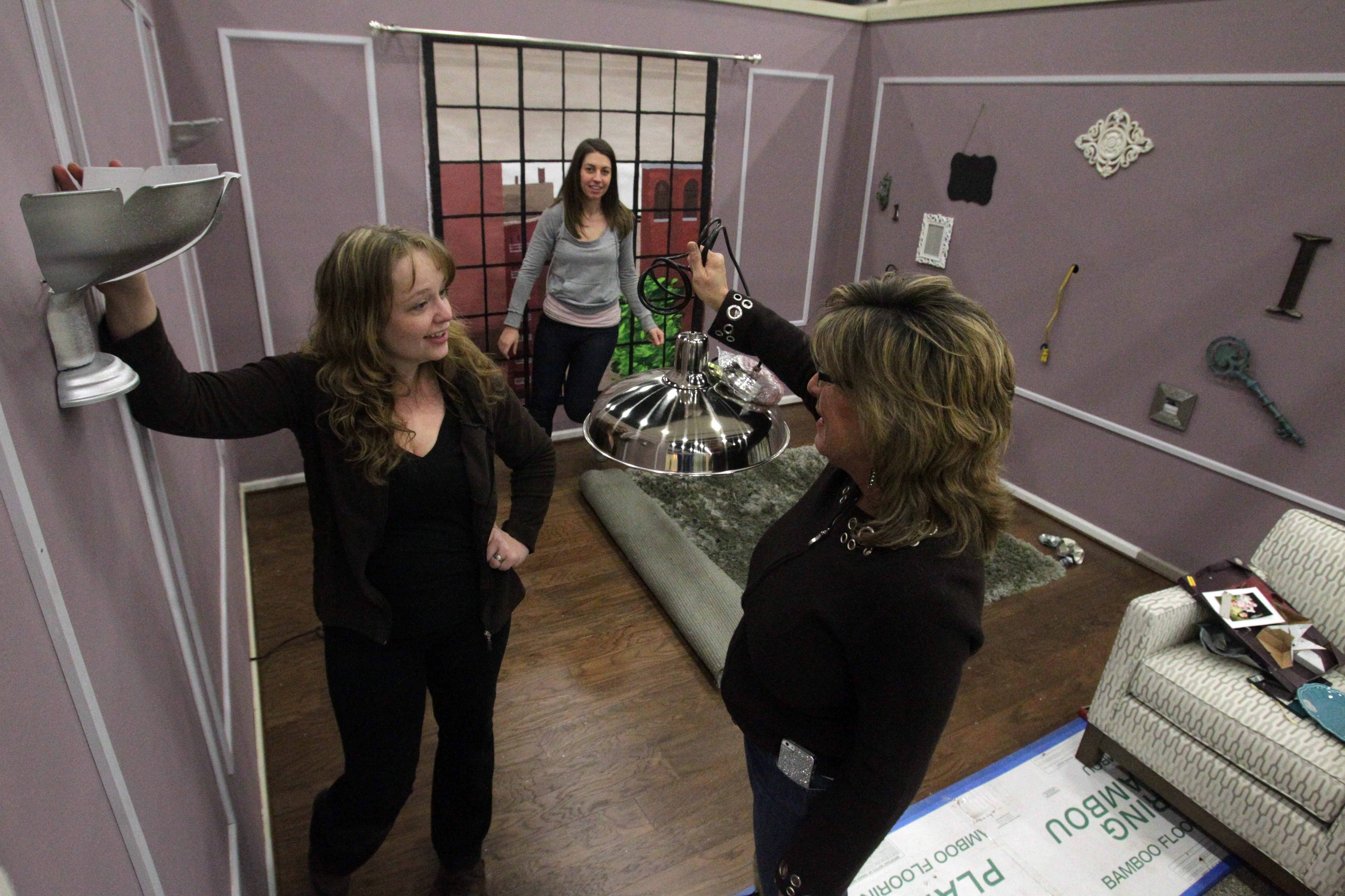 For the second year, the Interior Design Association of WNY is taking on the White Room Challenge at the Buffalo Home Show. Designer Laurel I. Swartz, above left, shows IDA President Michelle Peller White the wall sconce she made from the overhead shiny metal light. The original light is one of the mandatory design elements.