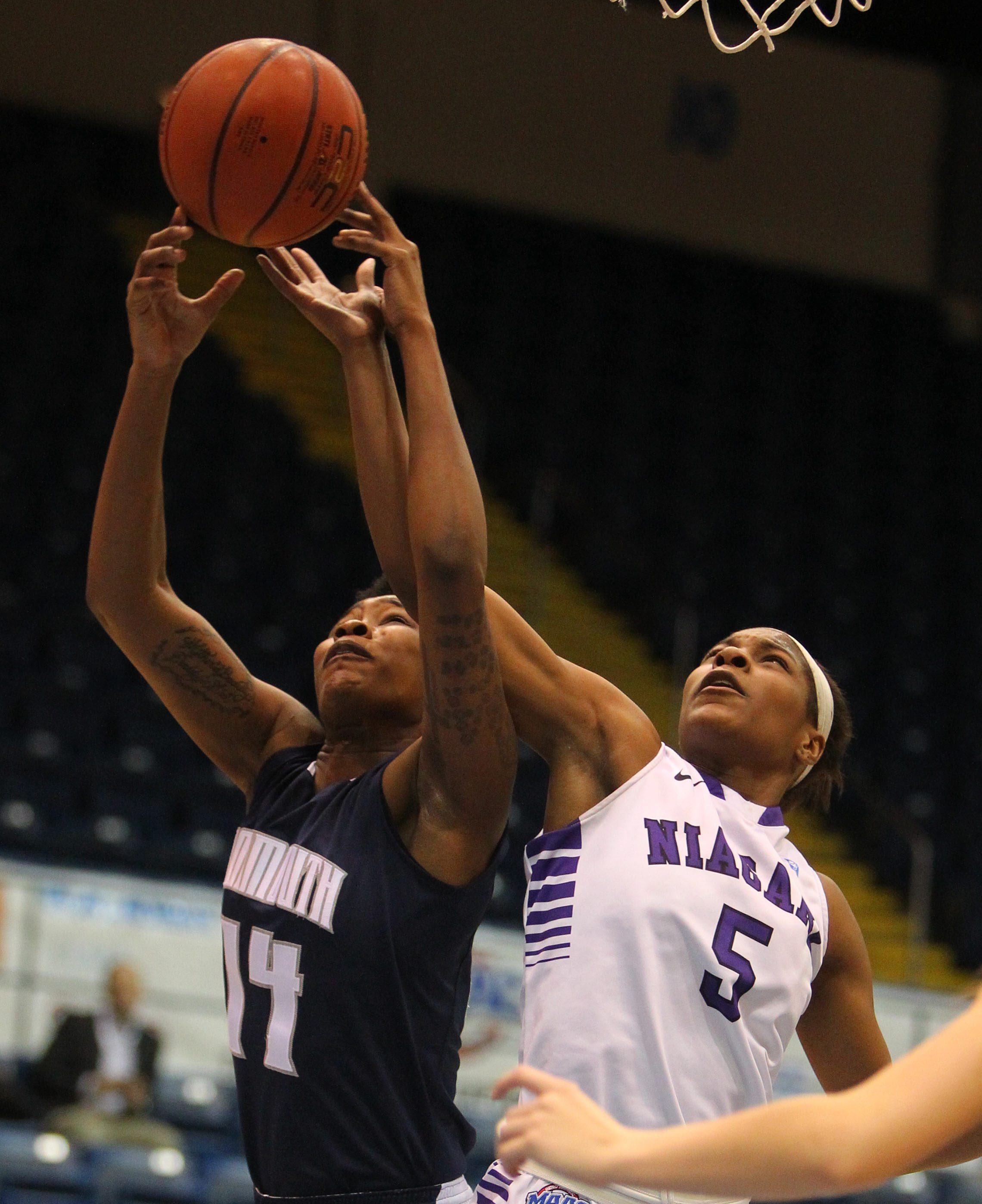 Niagara's Chanel Johnson reaches for a rebound with Monmouth's Christina Mitchell in the first half of the first round of the MAAC tournament at the MassMutual Center in Springfield, MA Thursday, March 6, 2014.    (Mark Mulville/Buffalo News)