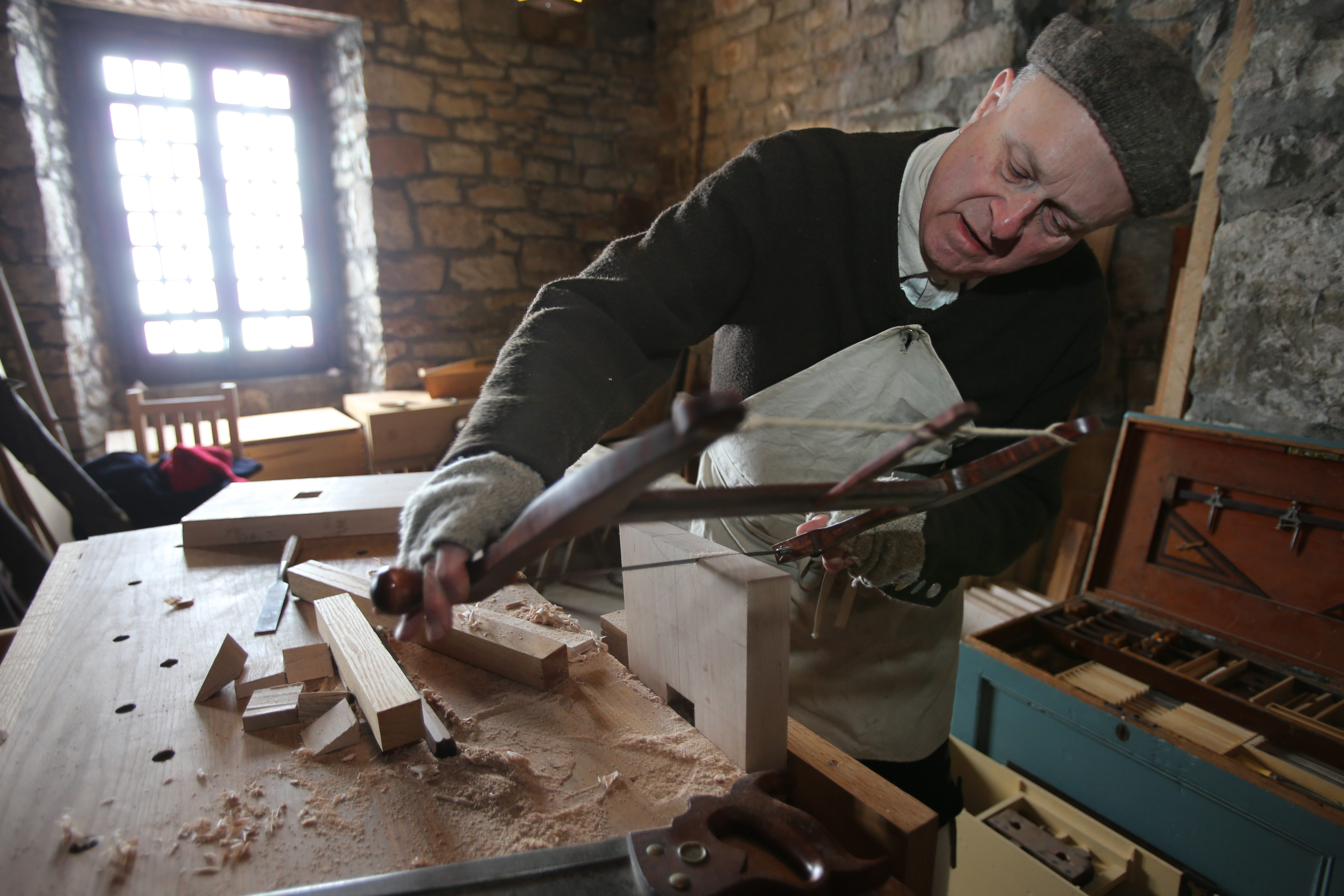 Robert Wiltshire, a master carpenter who has been named Volunteer of the Year, uses a saw in his woodshop in the French Castle at Old Fort Niagara in Youngstown.