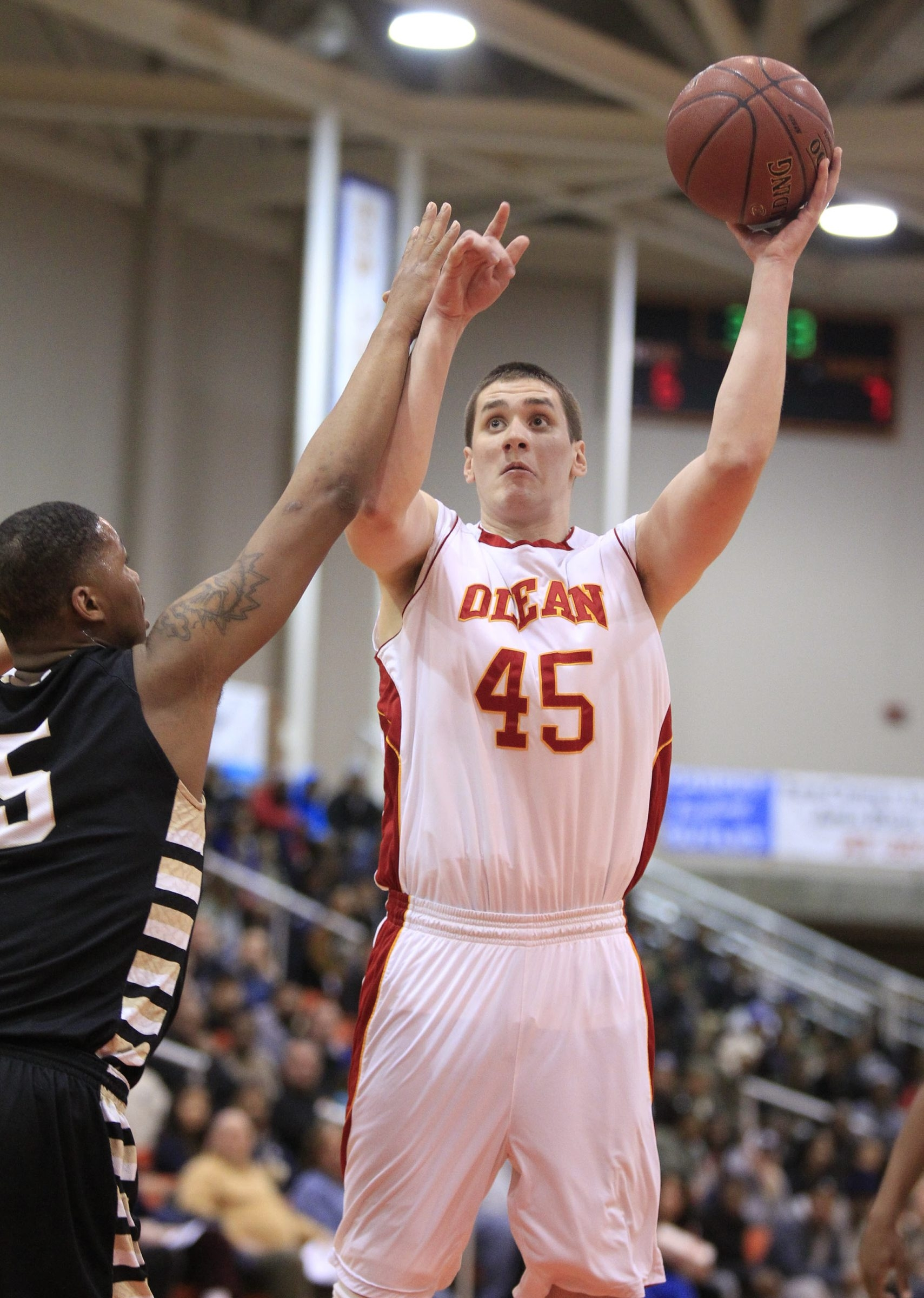 Olean Player,Sam Eckstrom shoots over East player Tyree Tyson (5) in the Class B final at Buffalo State.