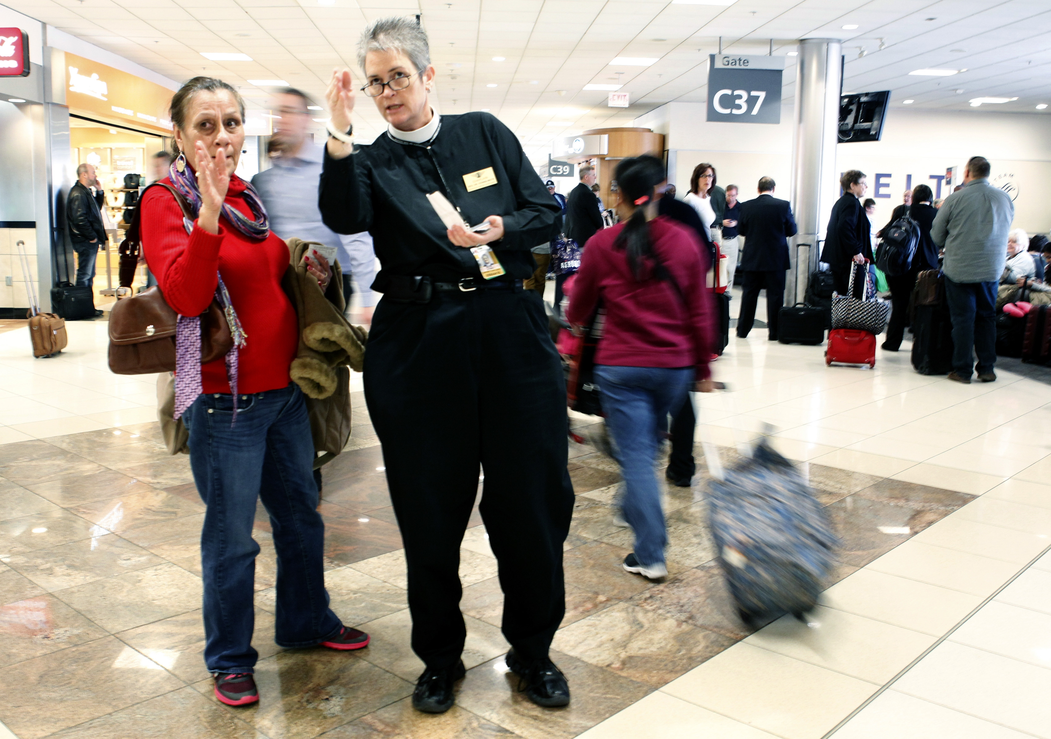 The Rev. Donna Mote points passenger in right direction as Atlanta airport chaplain.