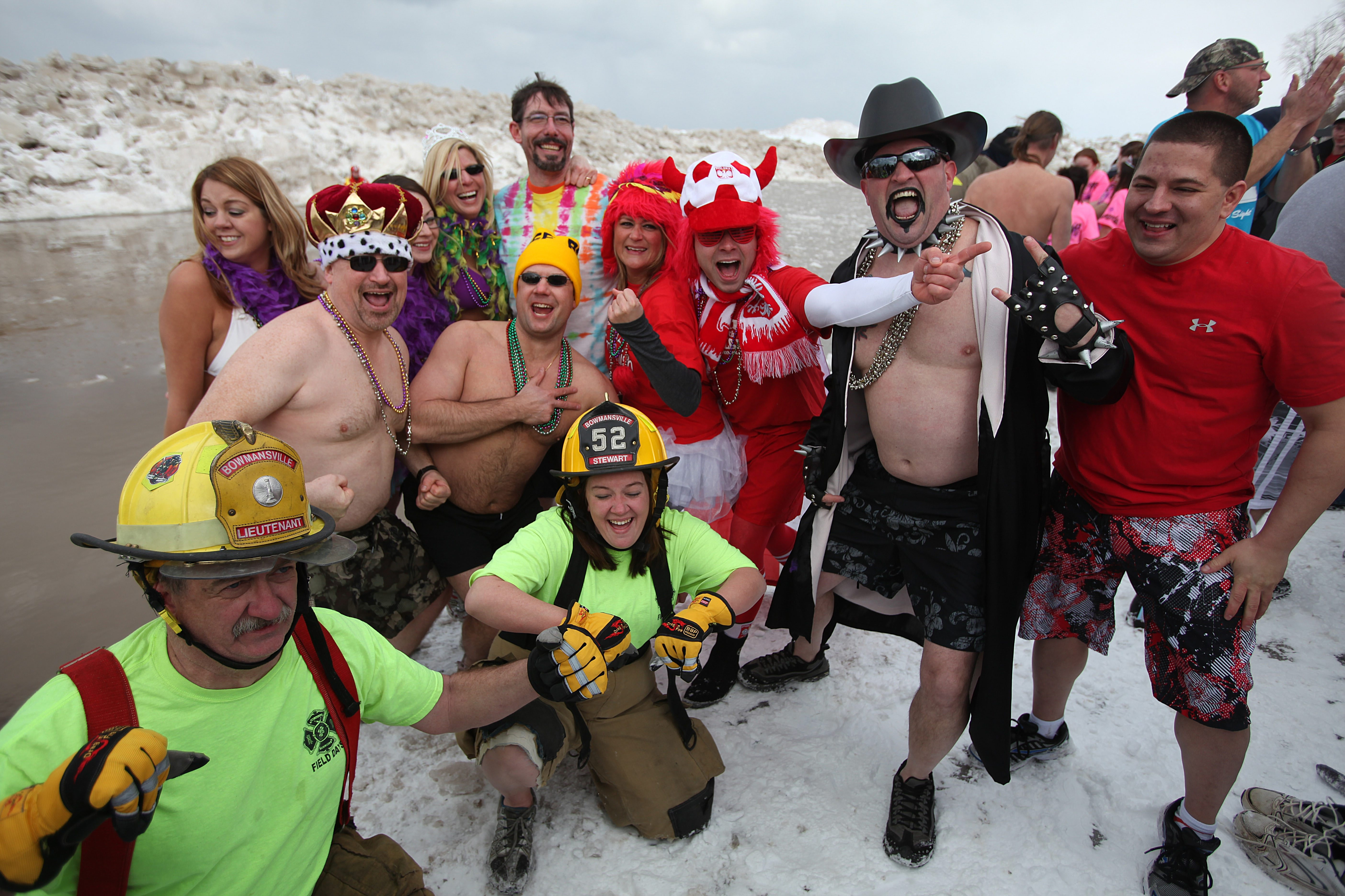 Clockwise from top: participants in zany costumes pose by the water at Olcott Beach during the 45th Polar Bear Swim for Sight, Sunday. Mindy Kramp, of Newfane, is all smiles as she gets wet next to a water rescue volunteer. Friends Kim Gordon, left, of Clarence, and Christy Zell, of Bennington, hug in the freezing Lake Ontario water.