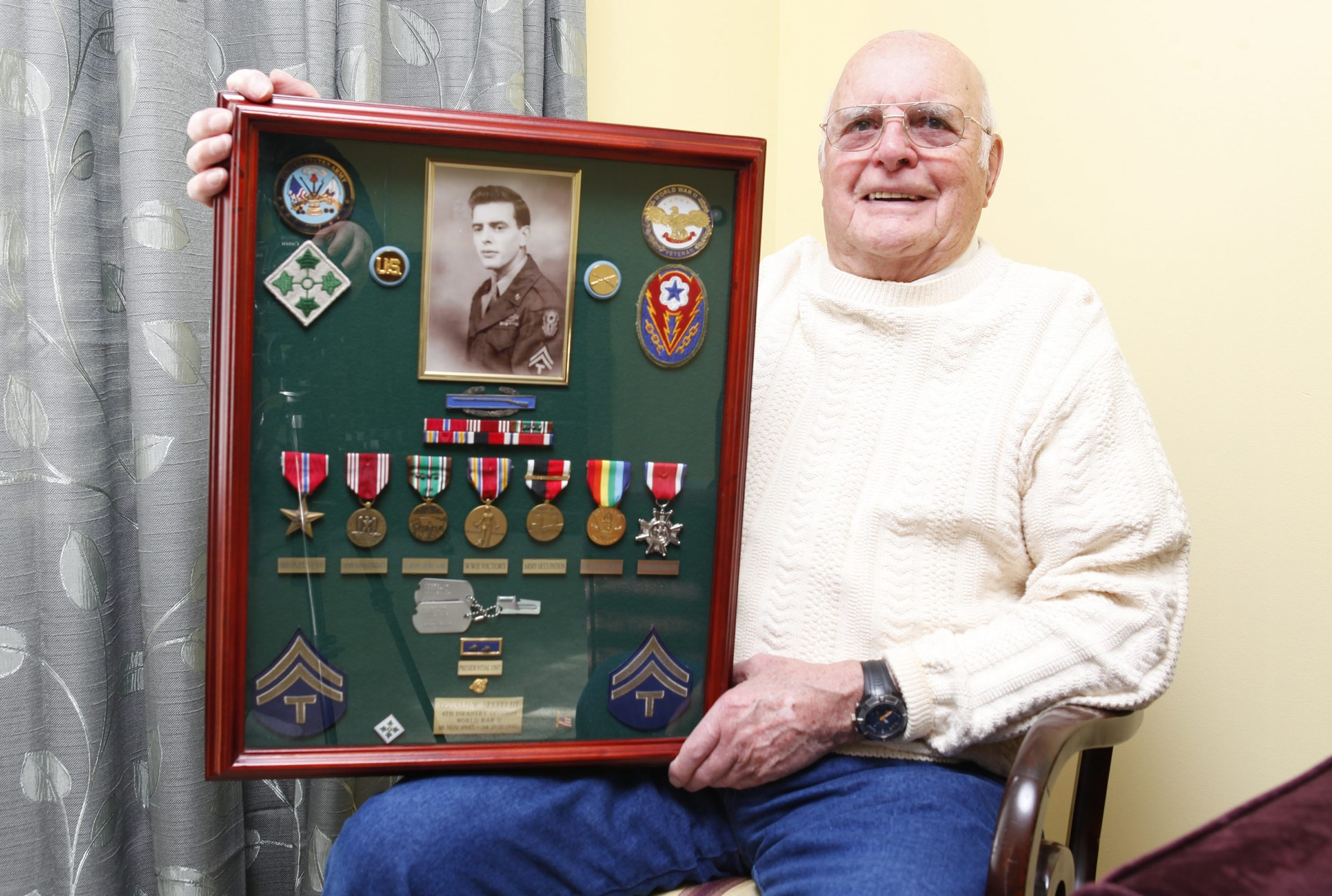 Medals and insignia from war in Europe evoke memories for Donald Seefeldt, whose battlefield trauma sent him to the hospital for 1½ months.