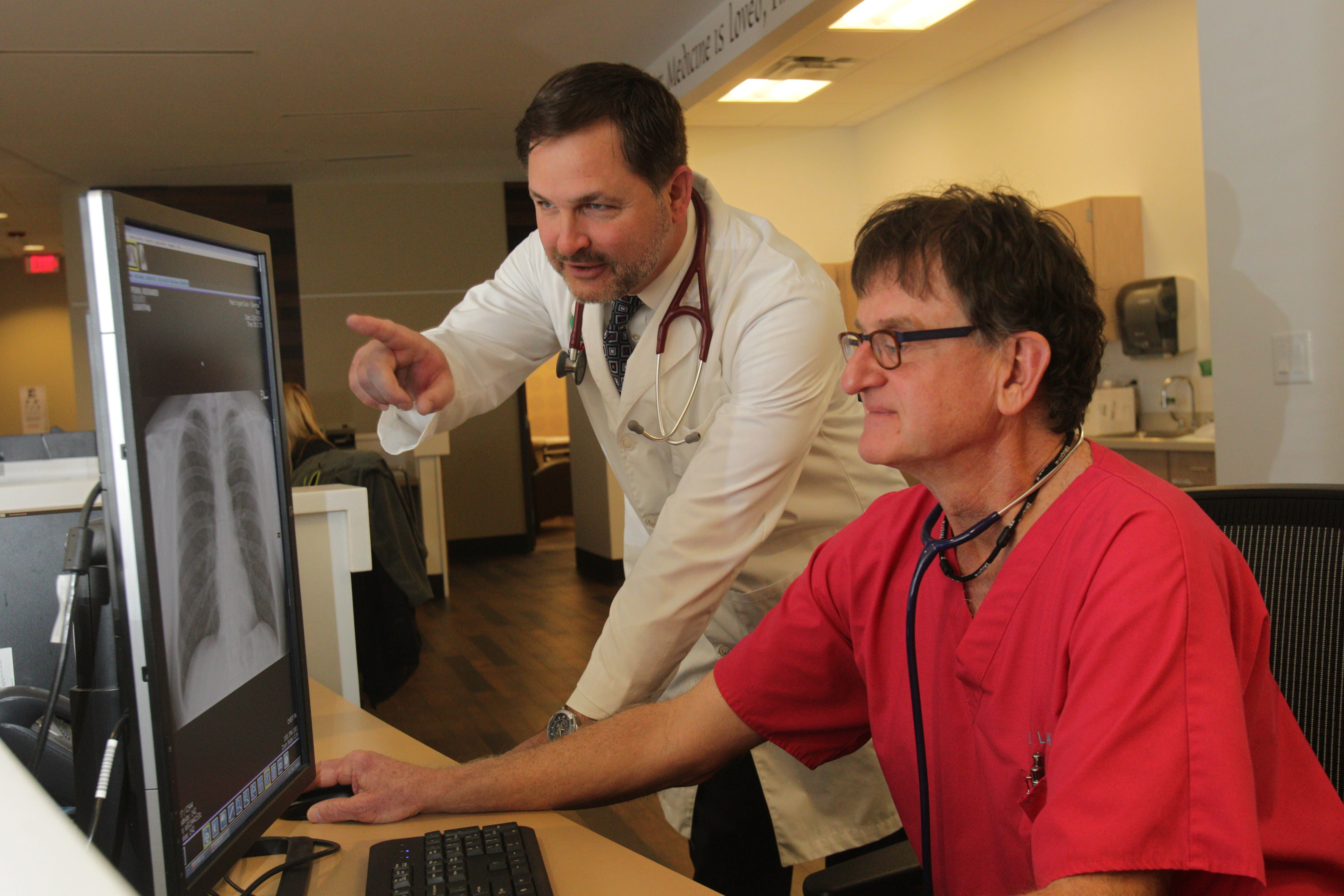 """""""Literally, by the time I walk out of my second patient room, I have all of the data on my first patient.""""— Dr. Mark Pundt, left, with Dr. Richard LaFountain"""