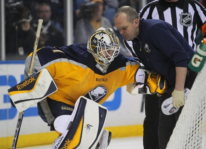 Sabres goalie Jhonas Enroth is helped by trainer Tim Macre after being injured. (Mark Mulville/Buffalo News)