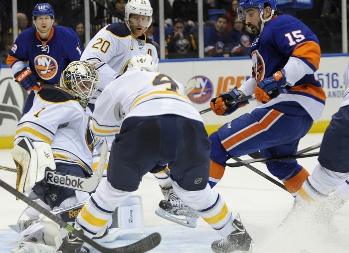 Buffalo Sabres goalie Jhonas Enroth (1) blocks a shot by the New York Islanders' Cal Clutterbuck (15) as Sabres' Henrik Tallinder (20) and Jamie McBain converge during the second period in Uniondale. (AP Photo/Kathy Kmonicek)