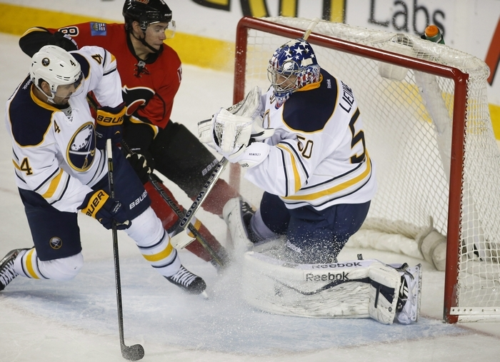 Sabres goalie Nathan Lieuwen, right, grabs the puck on a shot by Calgary's Joe Colborne during Tuesday's game at Scotiabank Saddledome.  (AP Photo/The Canadian Press, Jeff McIntosh)
