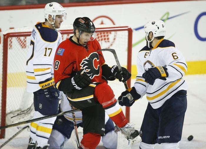 Sabres Torrey Mitchell, left, and Mike Weber, right, look on as the Flames' Joe Colborne celebrates his goal during the second period. (Associated Press)