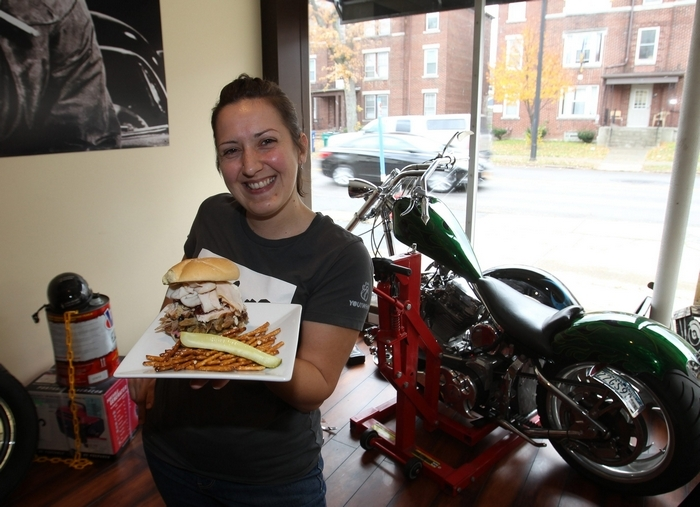 Cyndi Richert serves up one of the Garage Deli's large speciality sandwiches at the restaurant in Kenmore. (James P. McCoy/Buffalo News)