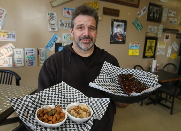 Owner and Chef Joe Tomasino proudly displays a half rack of ribs and both the sausage explosion and potato explosion sides, at J&L's Boulevard Barbecue in North Tonawanda. (Photos by Charles Lewis/Buffalo News)