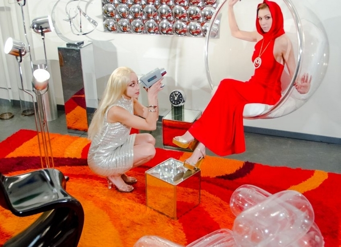 """In this promotional photo for the art exhibition """"The Future Is History,"""" models Zuri Appleby and Stephanie Elyse Luksch hang out in the exhibition's '60s-themed room."""