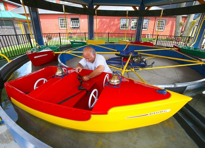 "Herschell Carrousel Museum volunteer Ron Witt attaches safety belts to the refurbished 1957 Wet Boat Ride  at the new ""Kiddieland Testing Park"" at the North Tonawanda museum on Wednesday. The park opens Saturday to the public.  Robert Kirkham/Buffalo News"